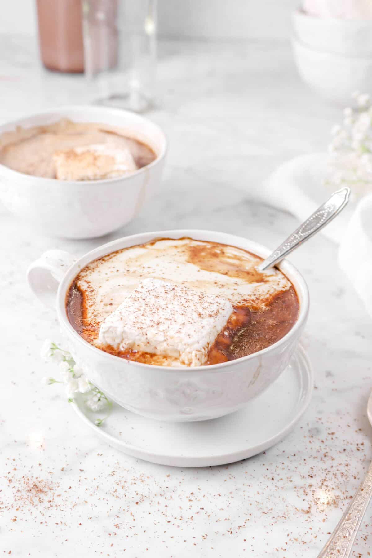 two mugs of hot chocolate with a spoon in one