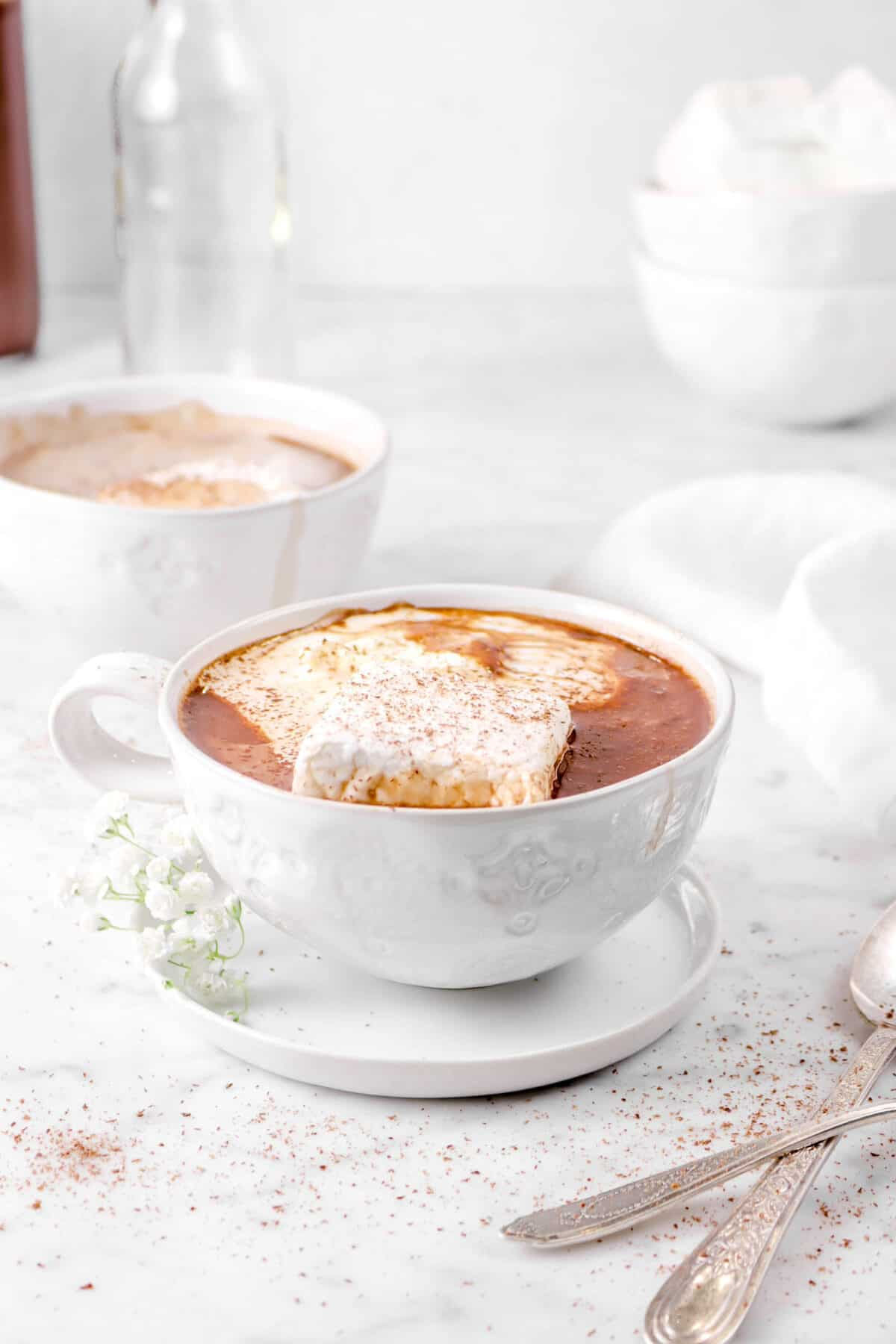 two mugs of hot chocolate on marble counter with two spoons and grated chocolate
