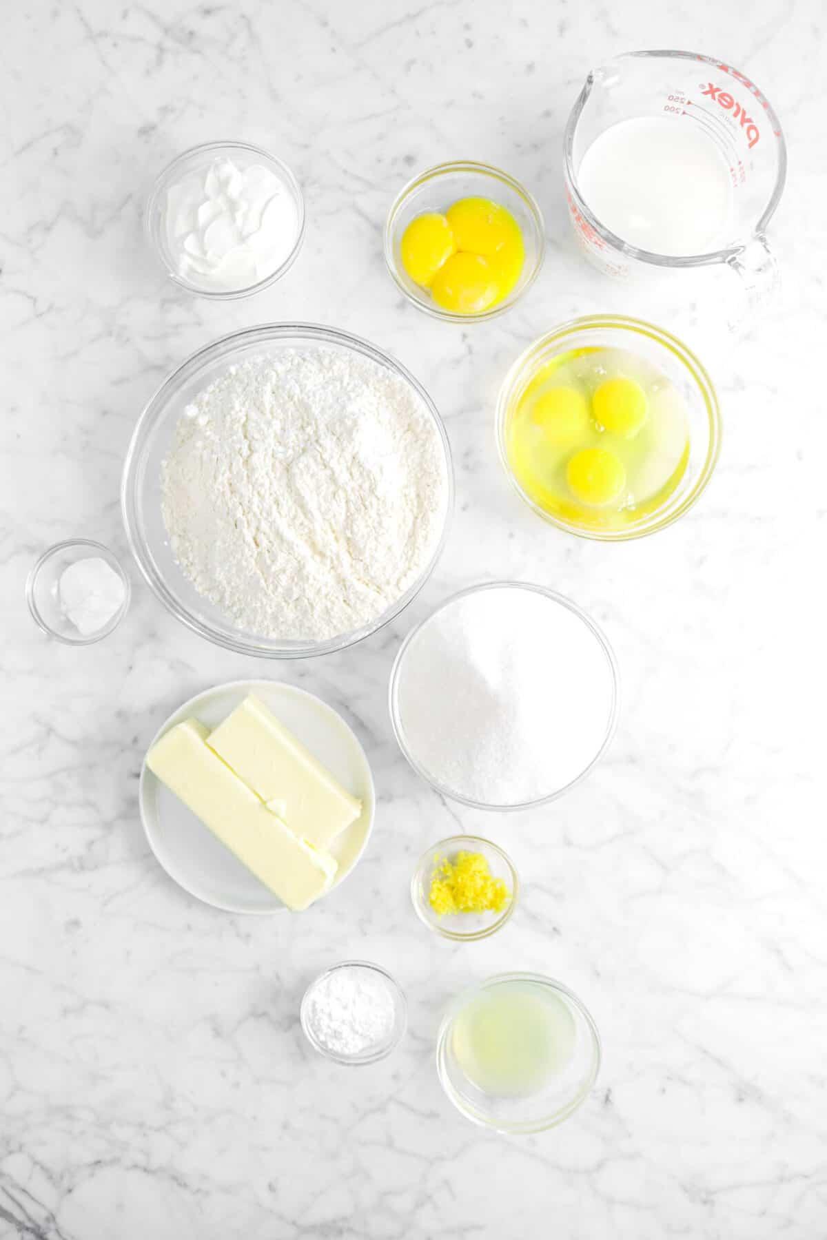 milk, egg yolks, eggs, sour cream, flour, sugar, baking powder, butter, lemon zest, lemon juice, and baking soda in glass bowls