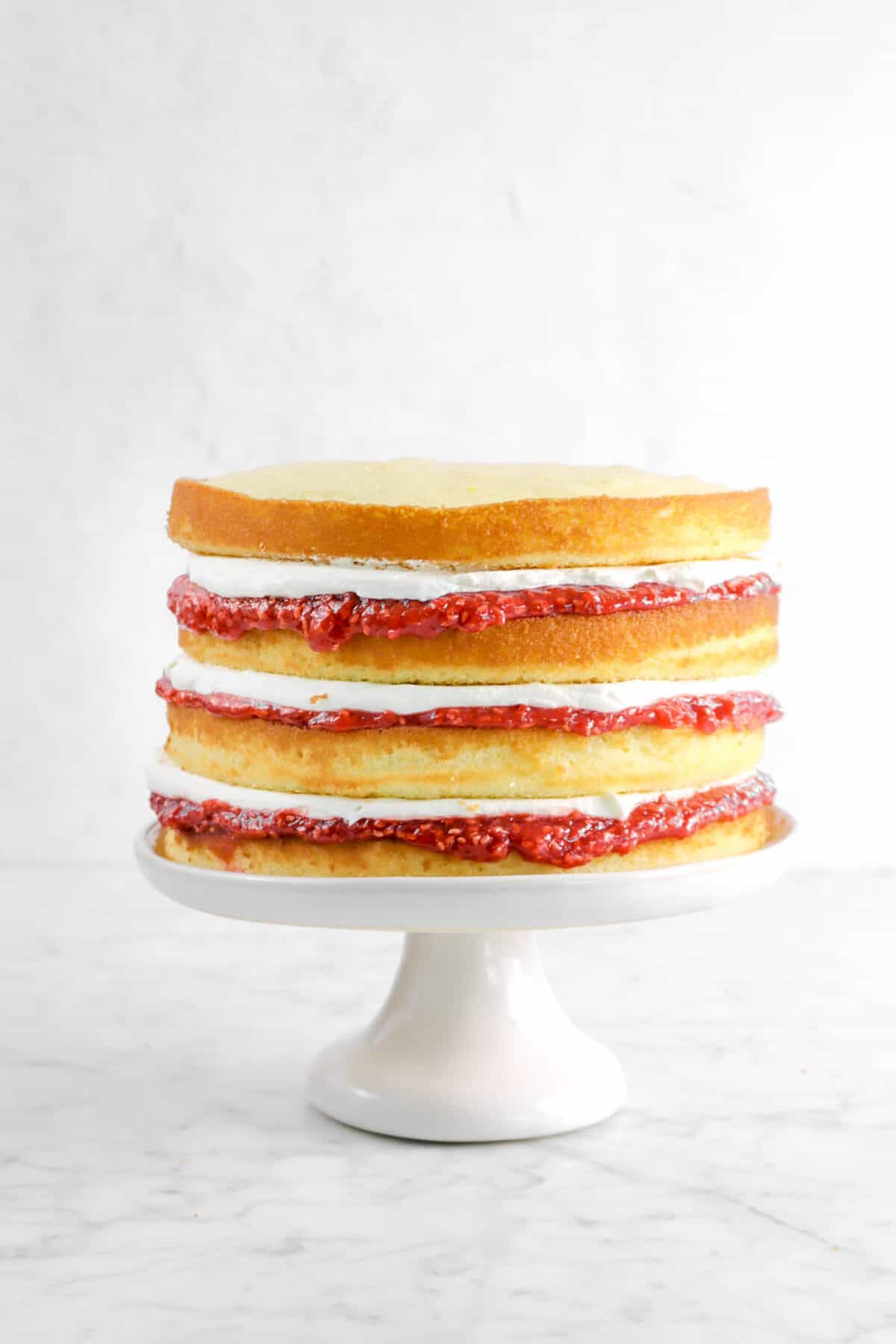 four layers of lemon cake with raspberry jam and chantilly cream