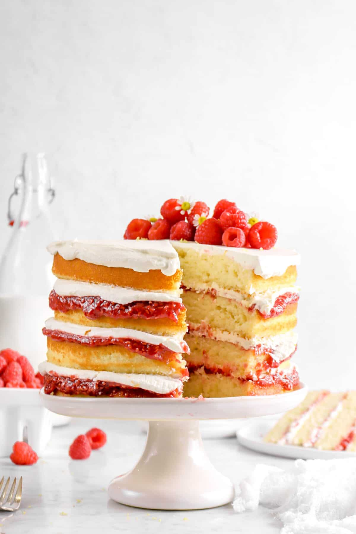 lemon and raspberry jam cake with a slice taken out of it on a white cake plate