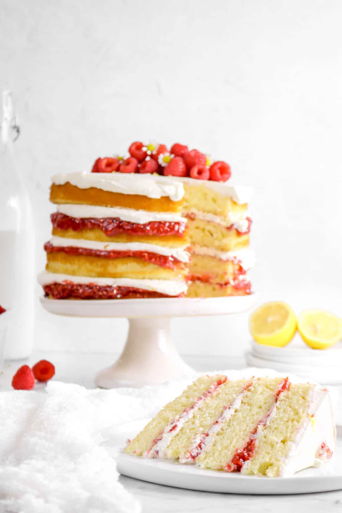 slice of lemon raspberry cake on a white plate with cake behind