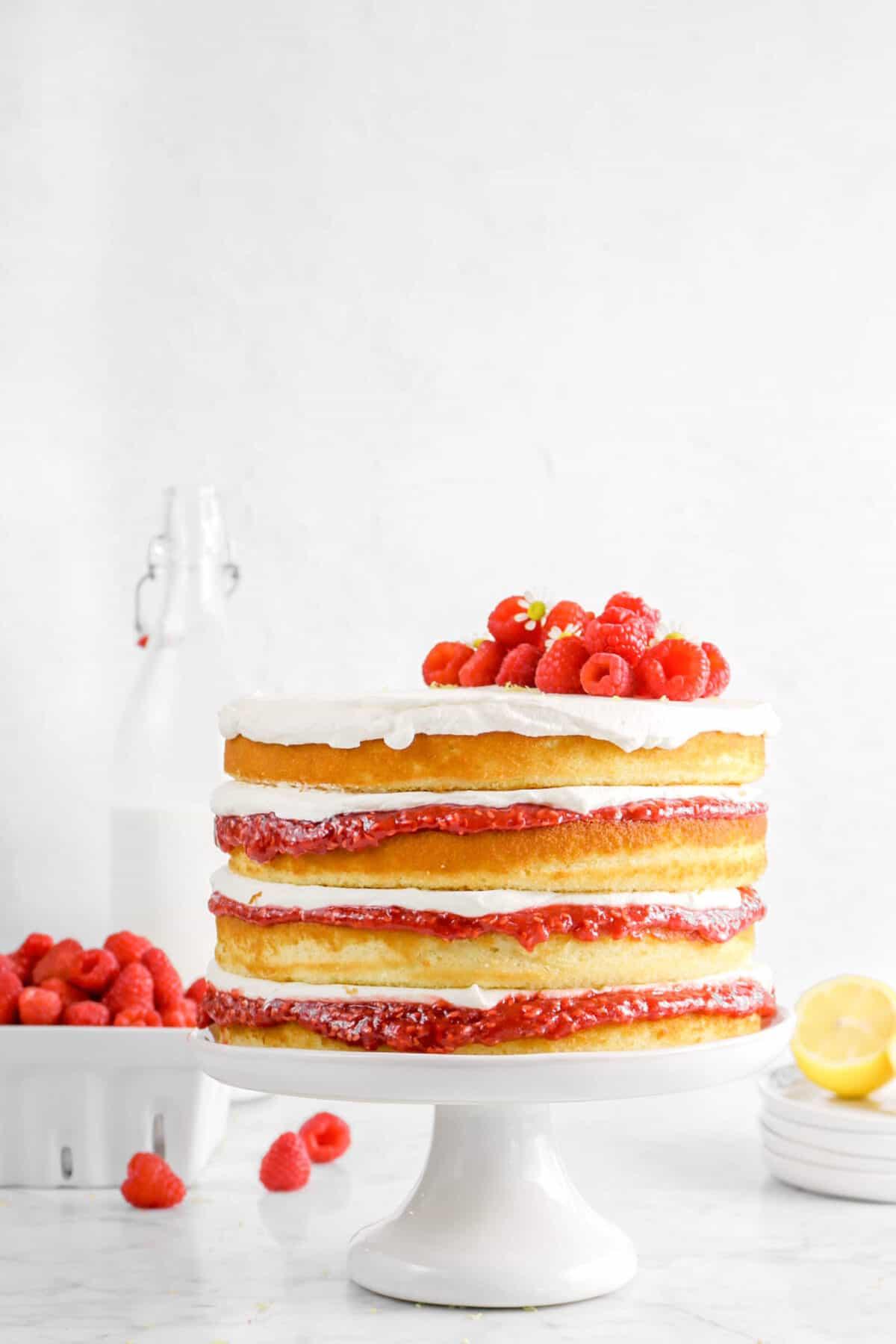 lemon raspberry cake on white cake plate with raspberries, lemon slice, and millk jug behind