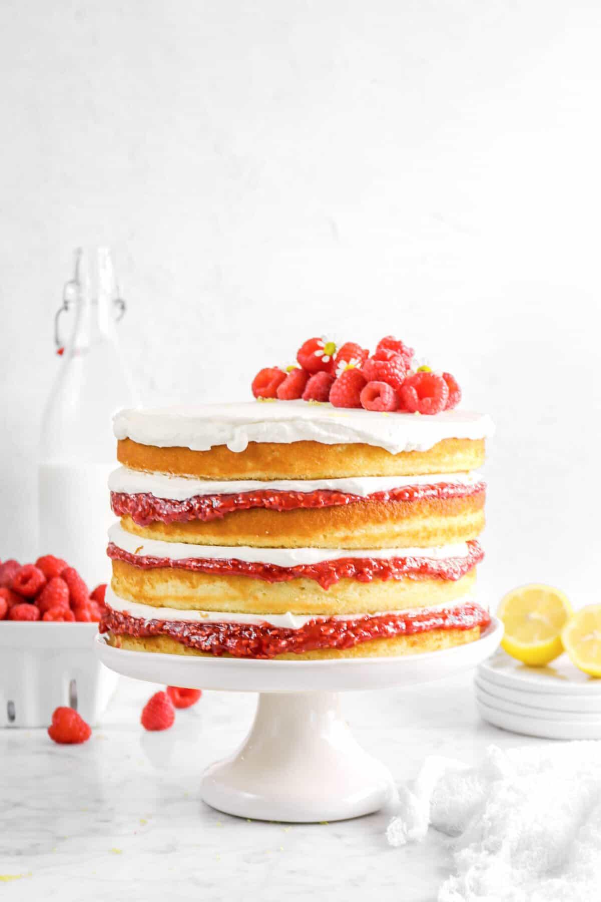 lemon raspberry cake on cake plate with lemons, raspberries, a cheese cloth, and milk
