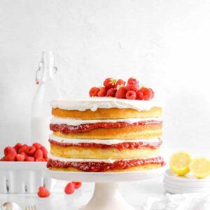 lemon raspberry jam cake on white cake plate with cheese cloth, forks, sliced lemon, raspberries, and milk