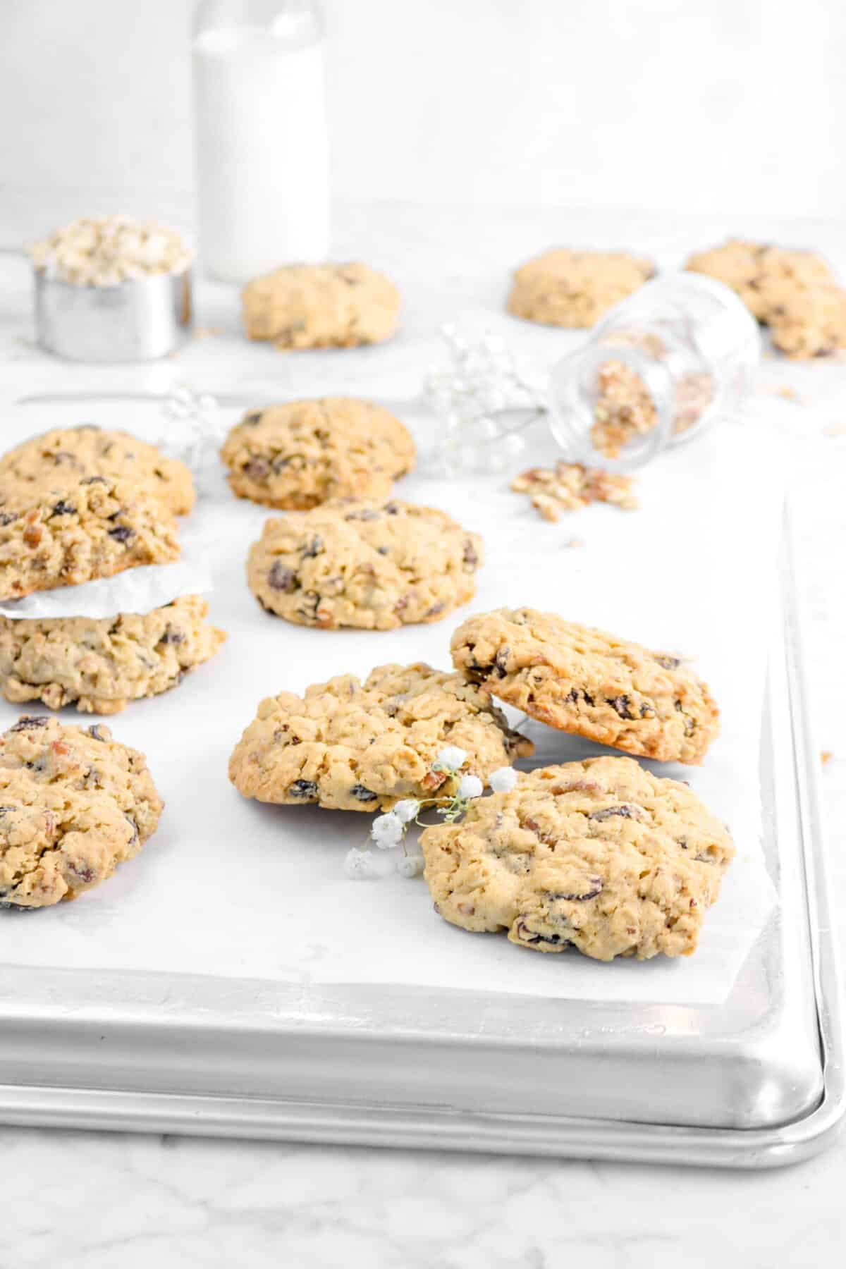 ten cookies on a sheet pan with chopped pecans and flowers, with more cookies behind