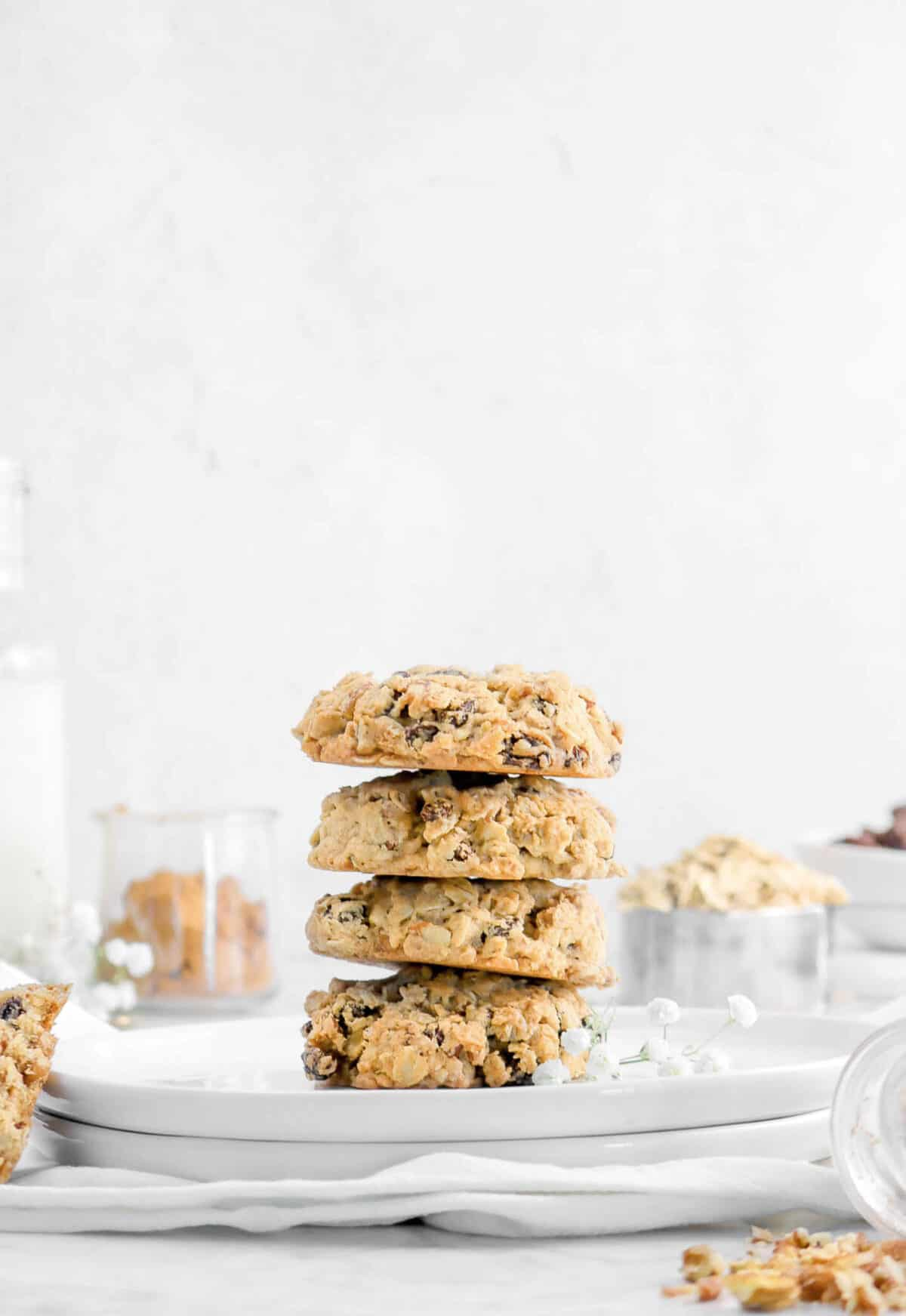 four cookies stacked on two white plates with milk, cinnamon, oats, and raising behind with flowers