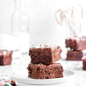 two brownies stacked on white plates with more brownies behind and candy canes
