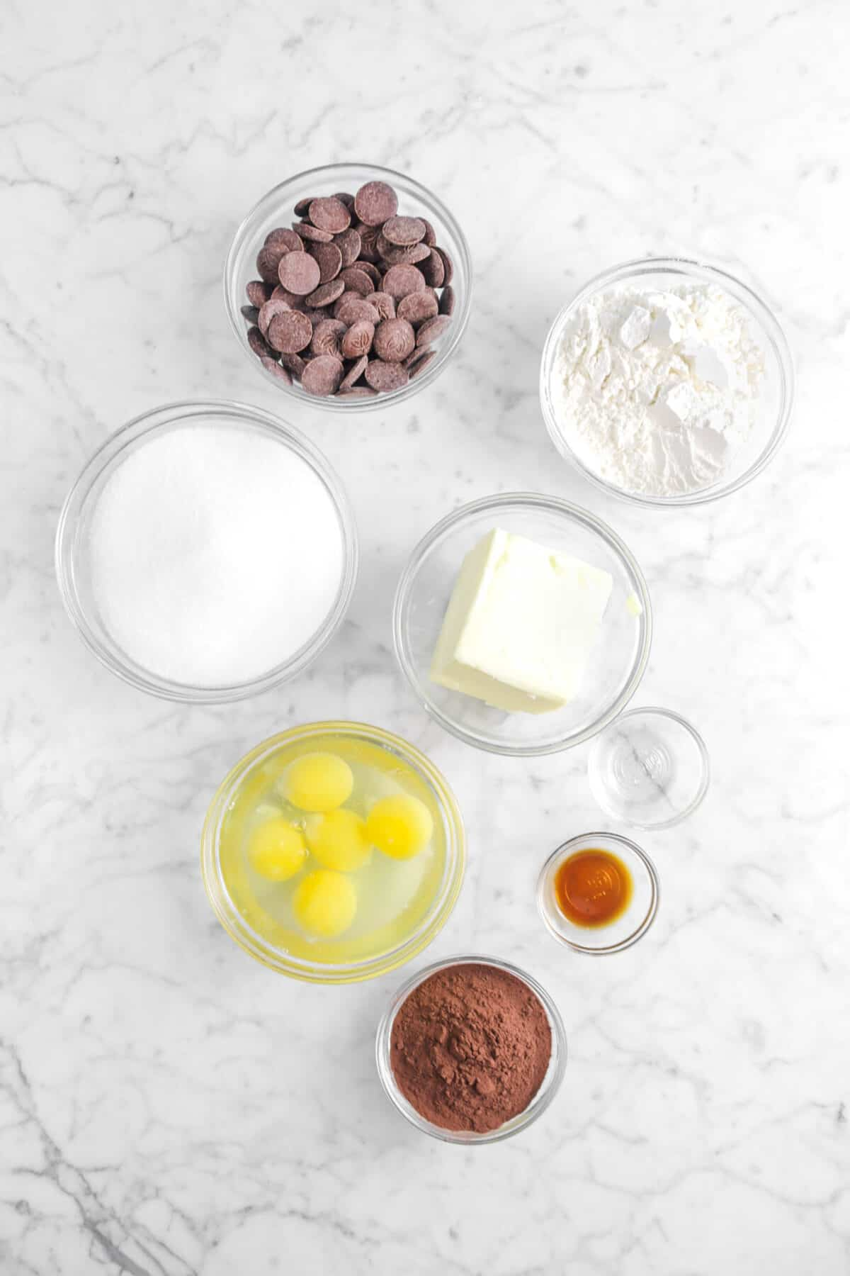 chocolate, flour, sugar, butter, eggs, peppermint oil, vanilla, and cocoa powder in glass bowls