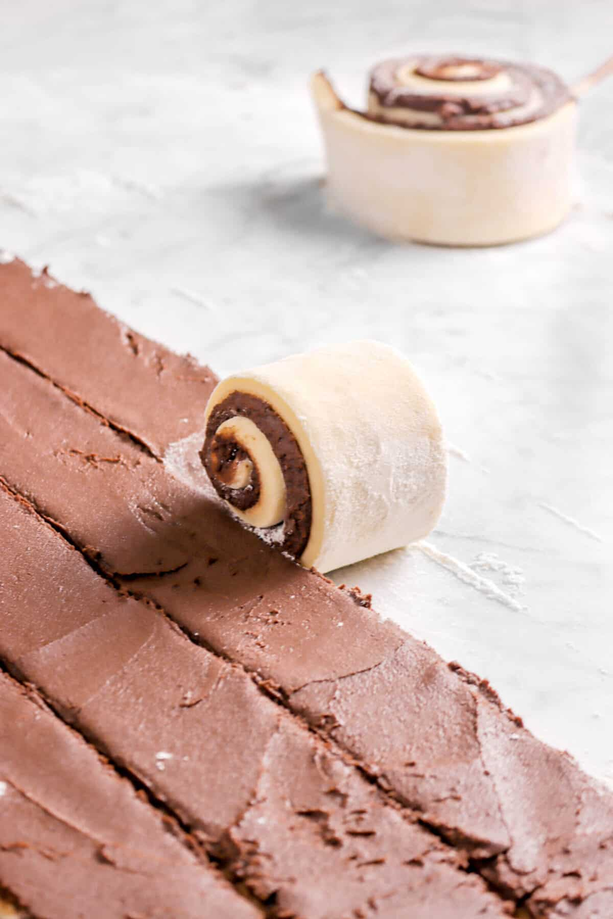 dough being rolled with sweet roll behind