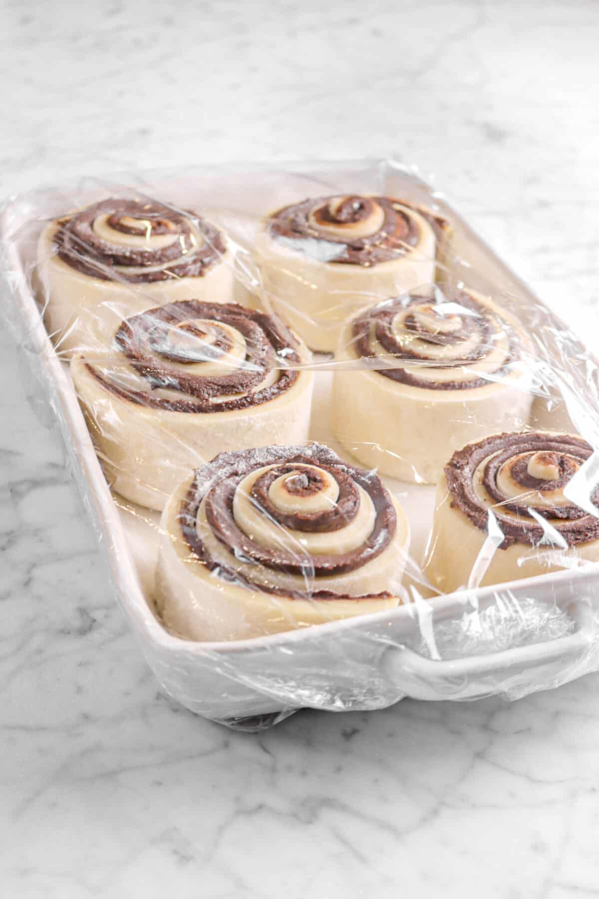 six rolls covered with plastic wrap in white casserole