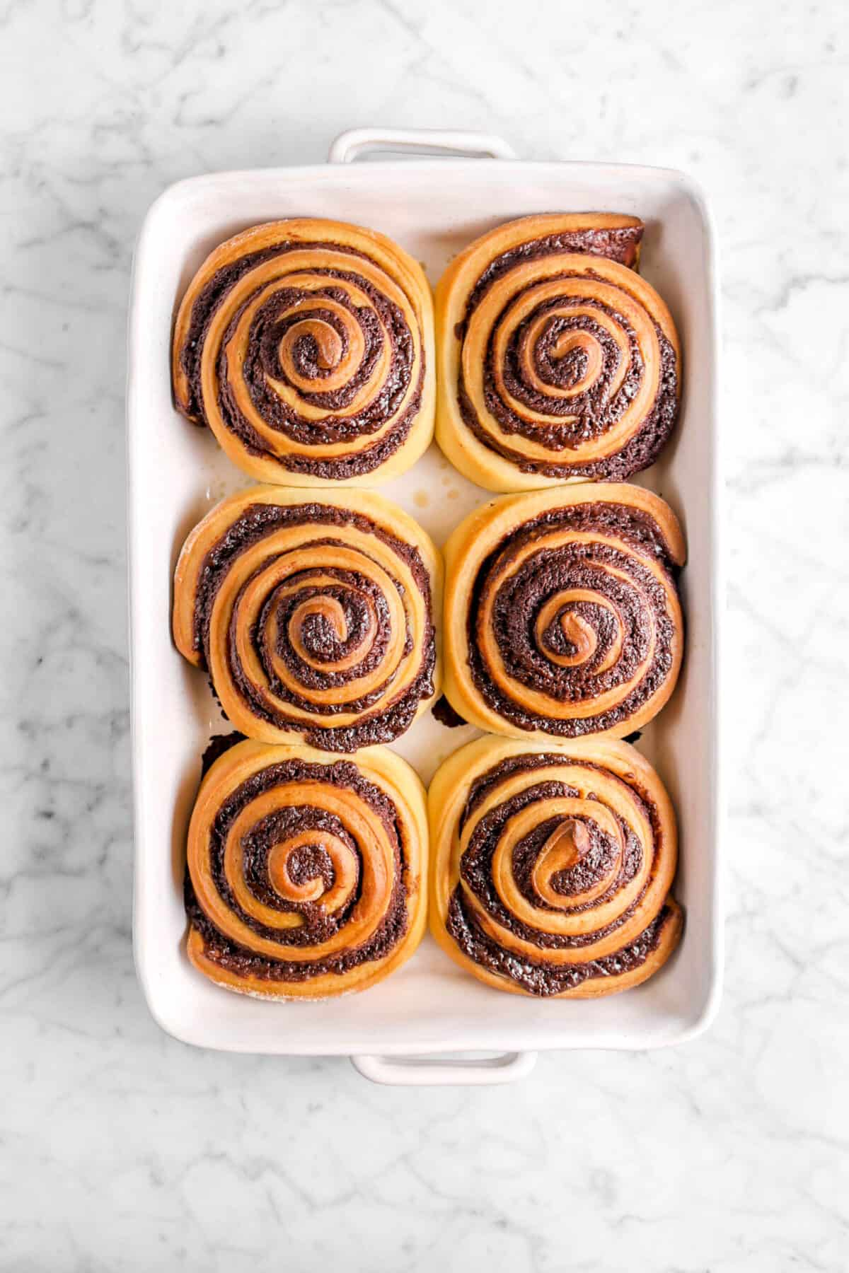 six baked chocolate sweet rolls in white casserole