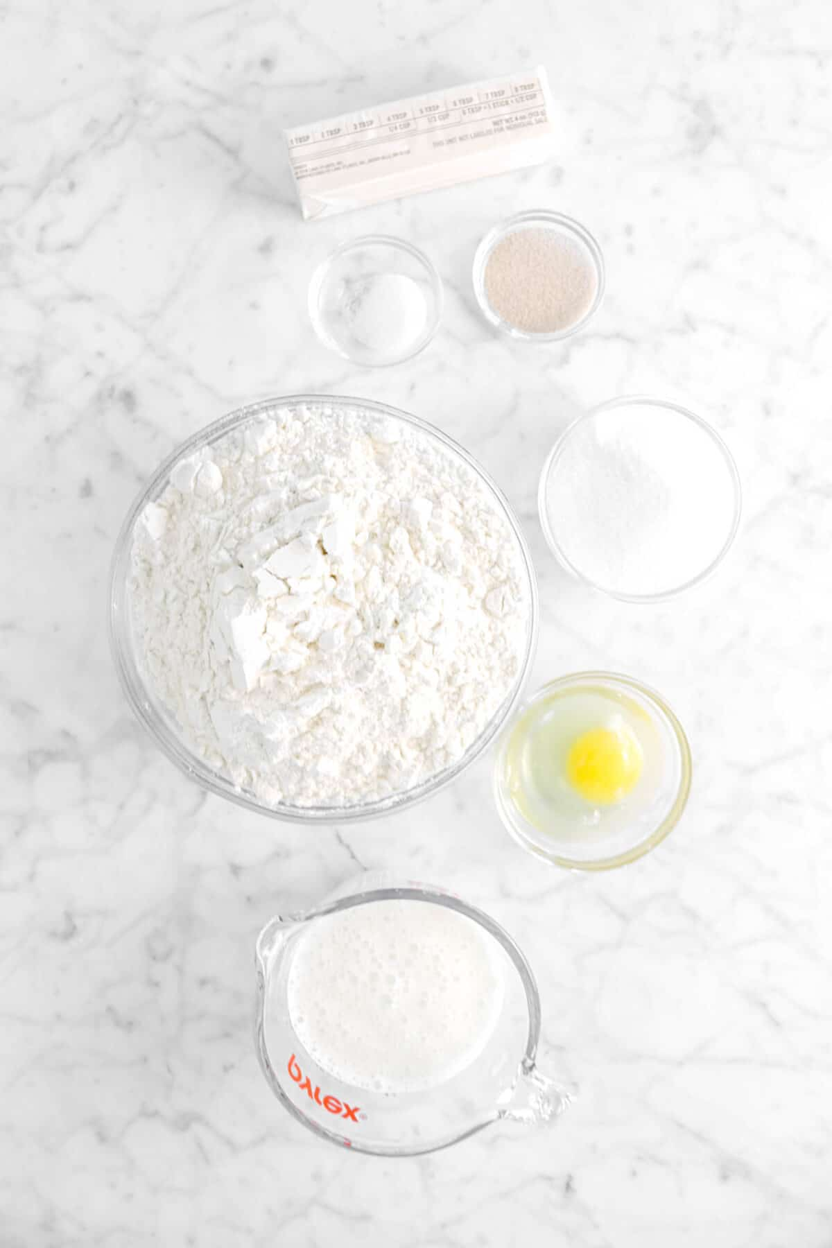 butter, salt, yeast, flour, sugar, egg, and milk on marble counter
