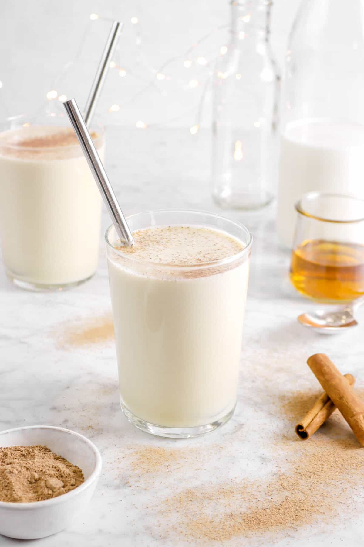 eggnog in glasses with cinnamon sticks, bowl of ground nutmeg, bourbon, and milk behind