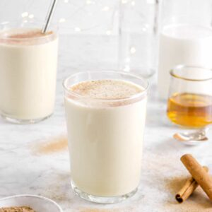 eggnog in two glasses with nutmeg on top with milk, bourbon, and cinnamon sticks