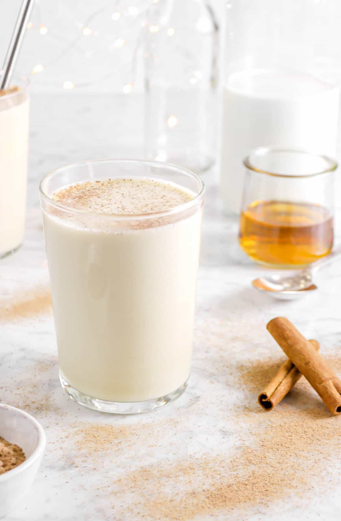 glass of eggnog with cinnamon sticks, spoon, bourbon, and milk behind