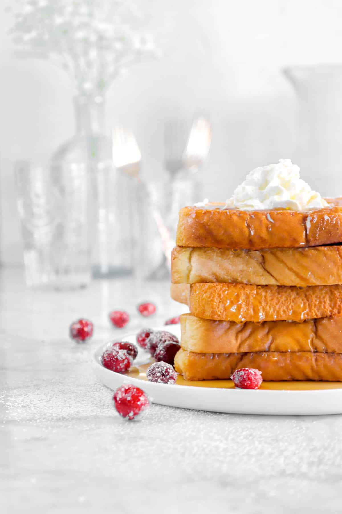french toast on a plate with glassed behind and cranberries