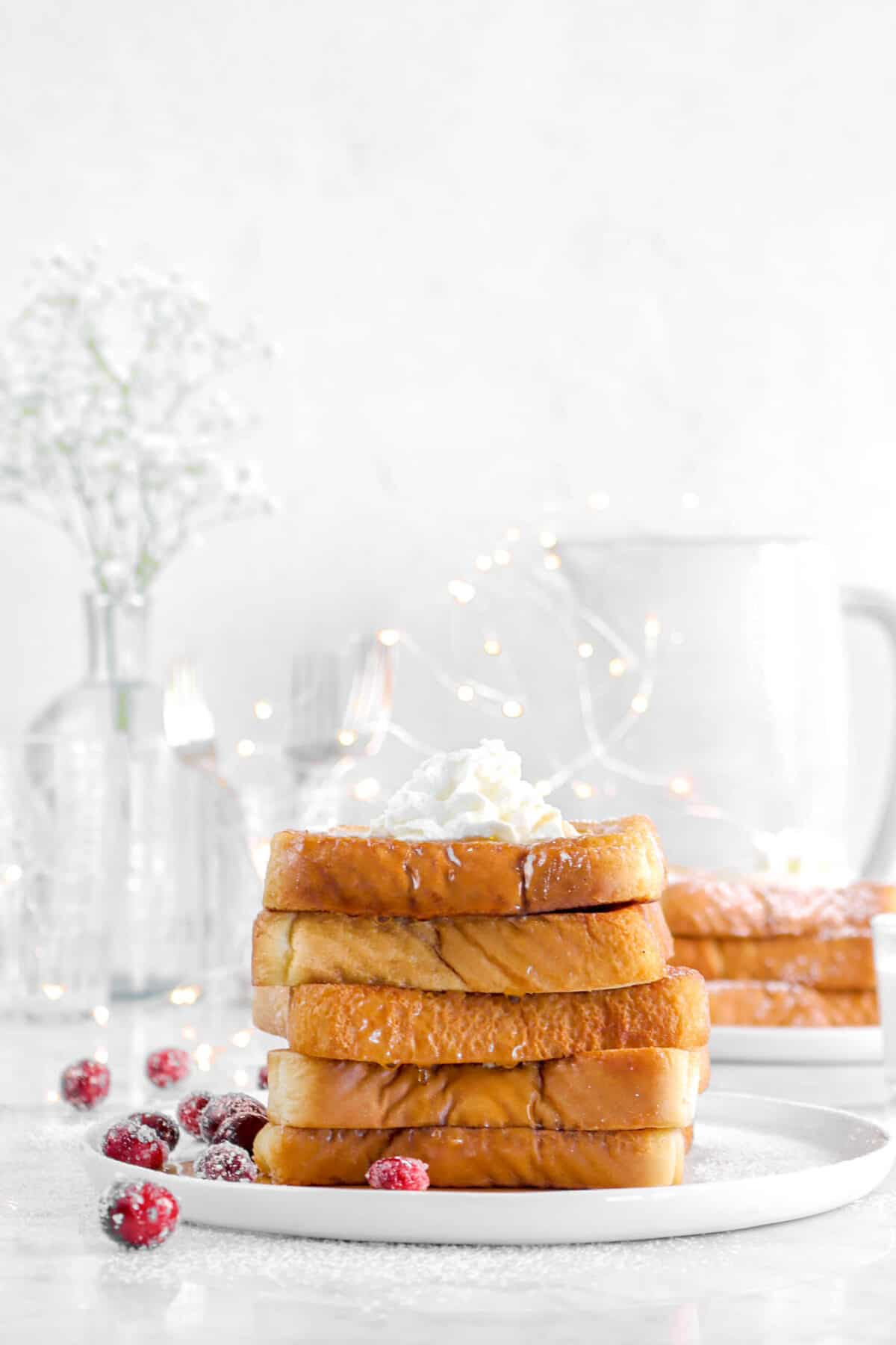 stacked french toast with fairy lights, glasses, and flowers behind