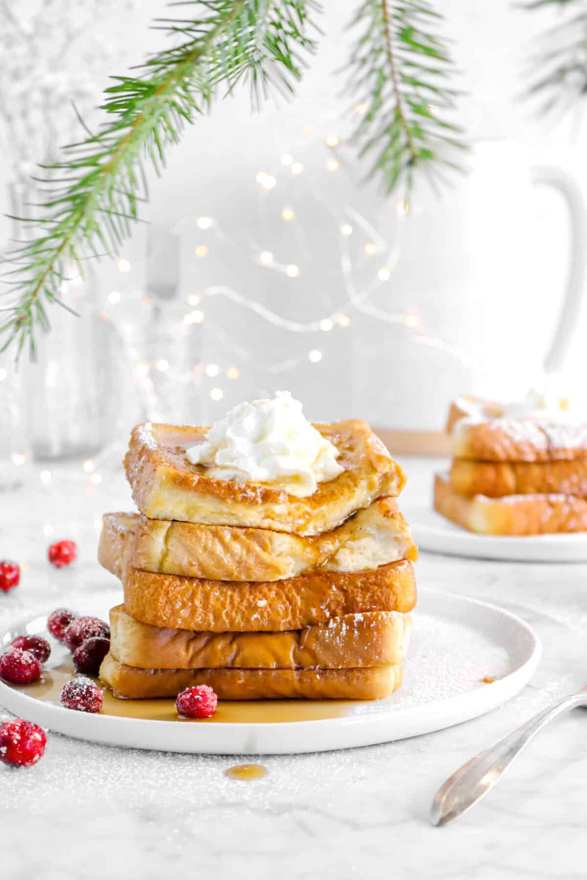 french toast on a white plate with greenery, more toast behind, fairy lights, and cranberries