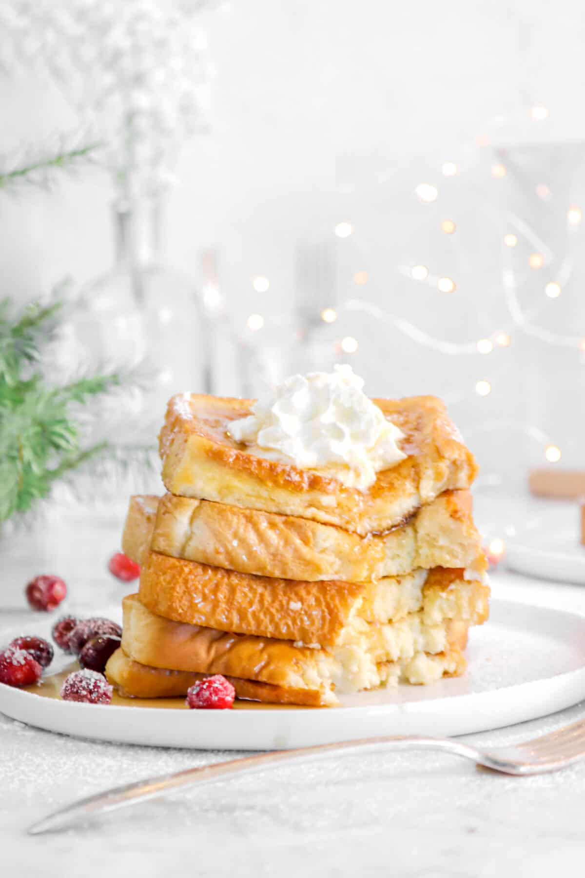 french toast on a white plate with fairy lights and a bite taken out