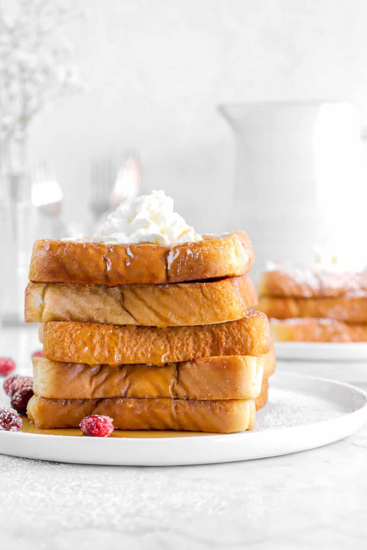 stacked french toast on a white plate with cranberries and whipped cream