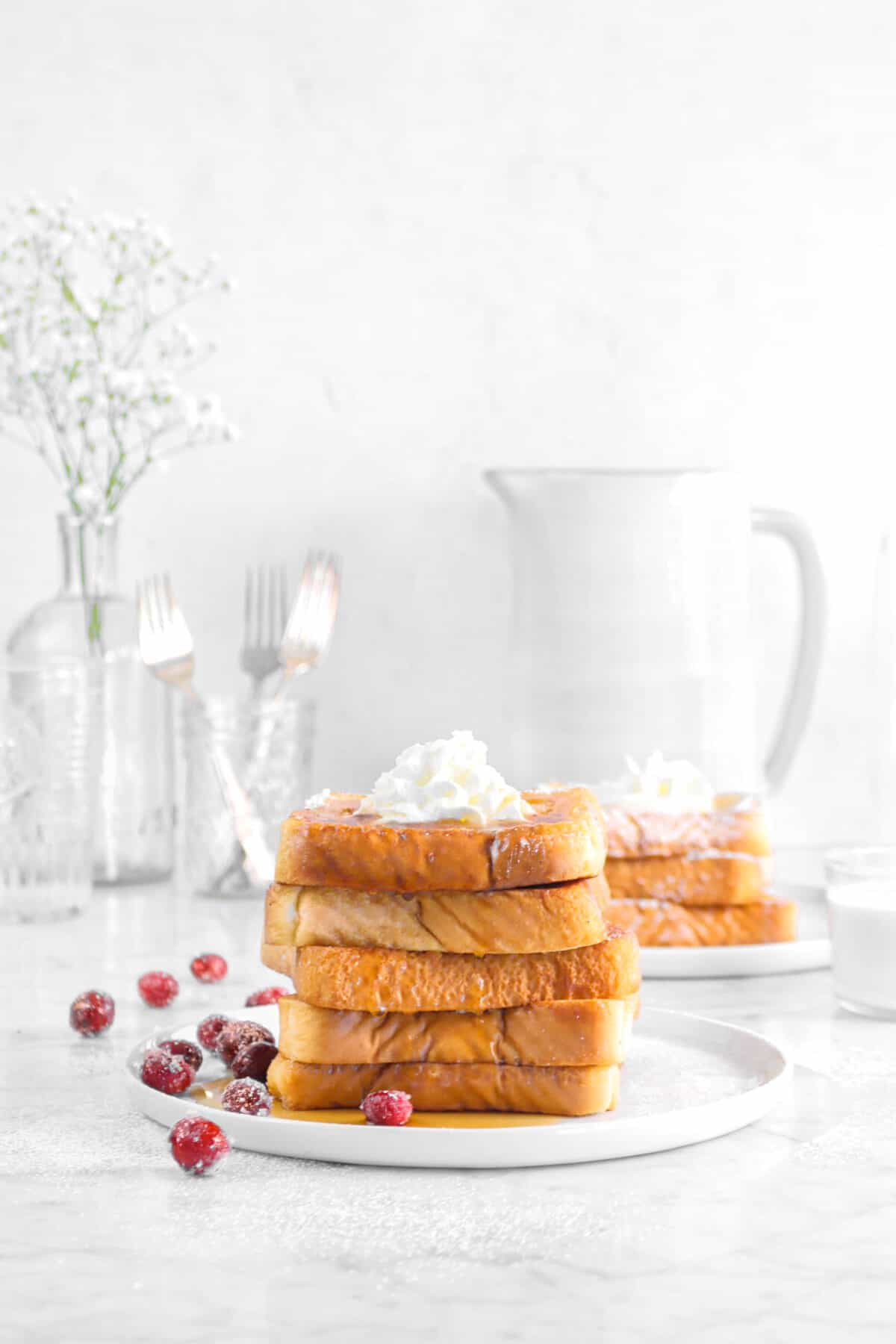 five pieces stacked french toast with cranberries, glasses, flowers, and pitcher