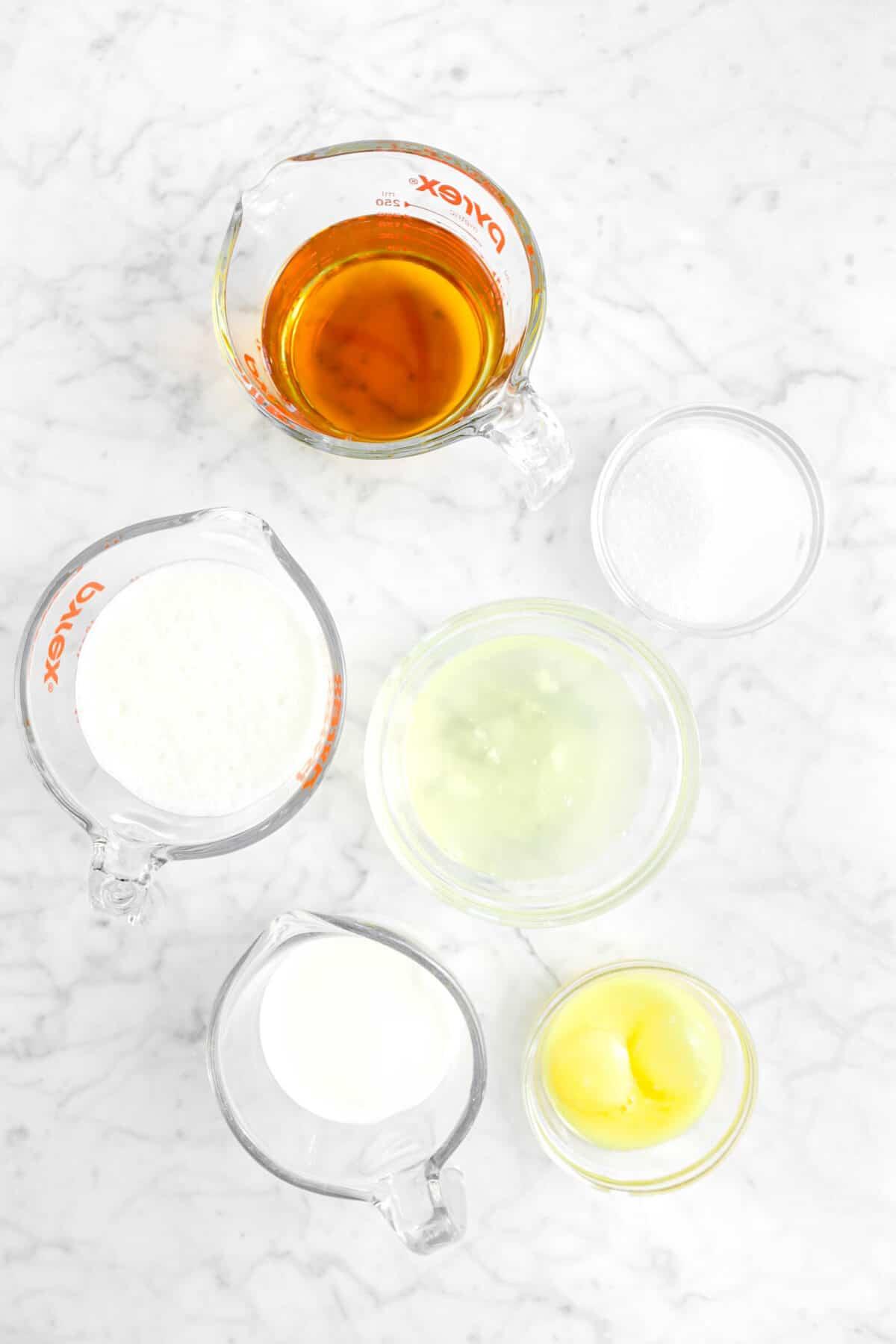 bourbon, sugar, heavy cream, egg whites, egg yolks, and whole milk on marble counter