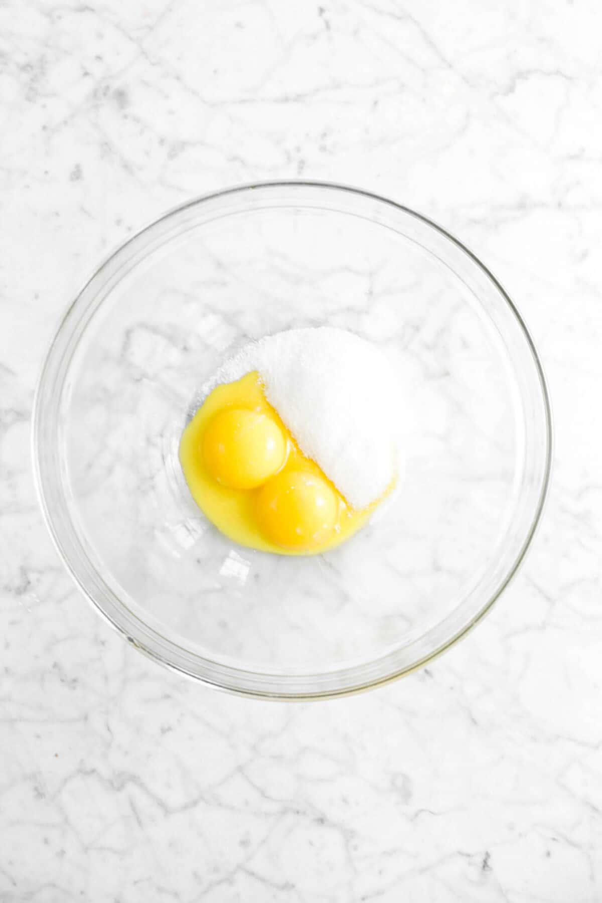 sugar and egg yolks in glass bowl