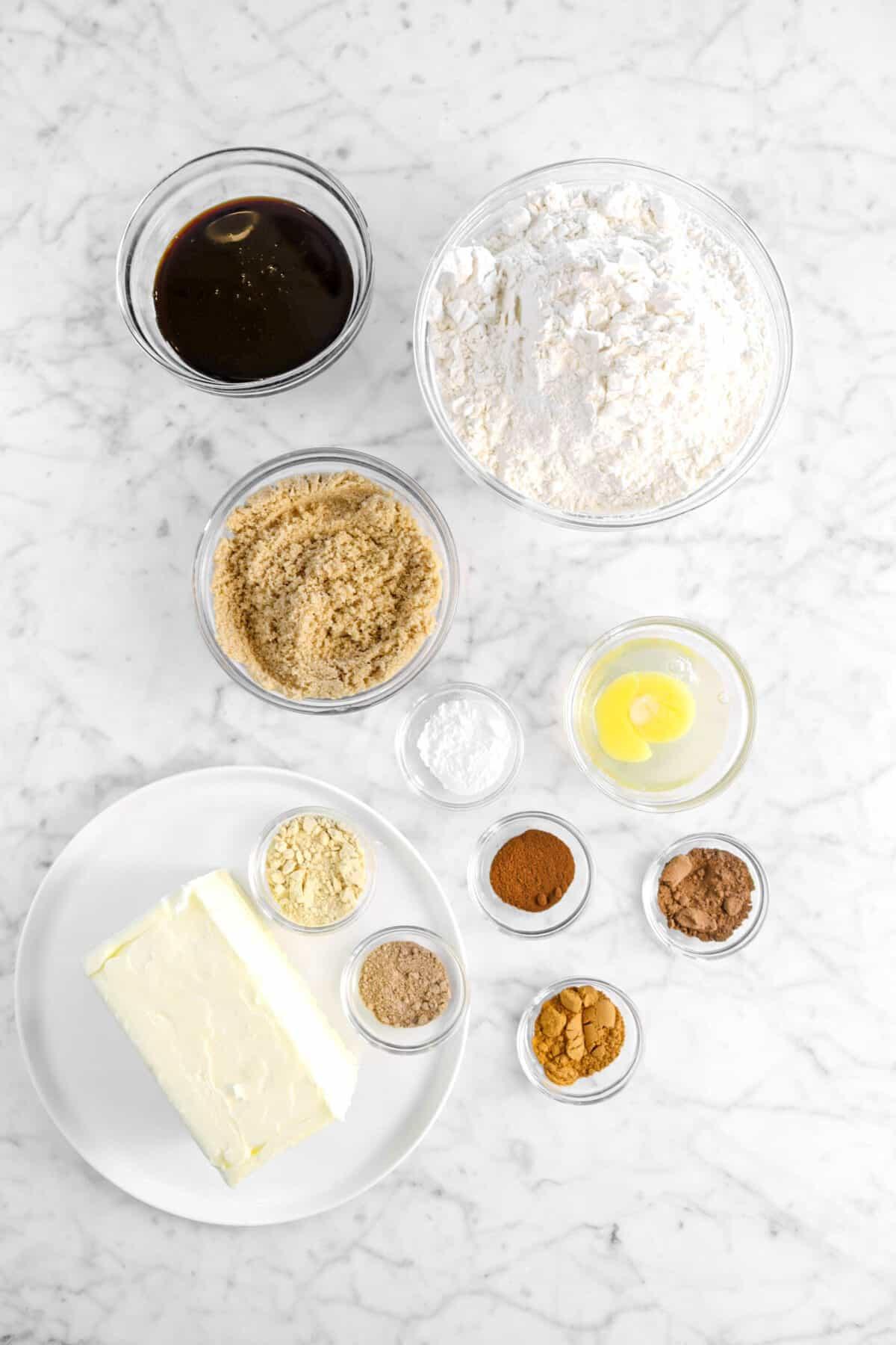 molasses, flour, brown sugar, egg, butter, baking soda, cloves, nutmeg, cinnamon, ginger, and allspice in glass bowls on marble counter