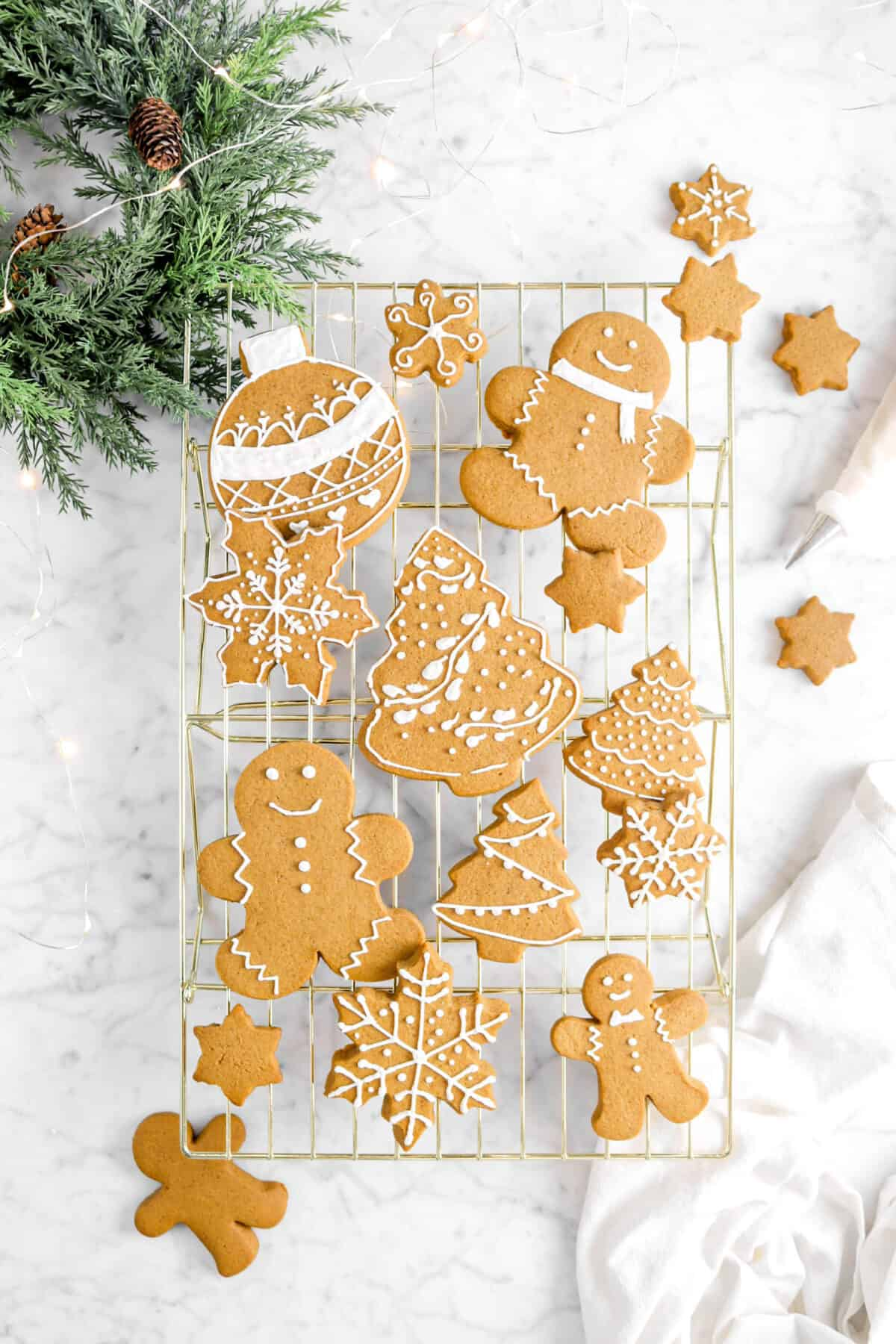 iced gingerbread cookies on gold cooling rack with napkin, greenery, lights, and piping bag