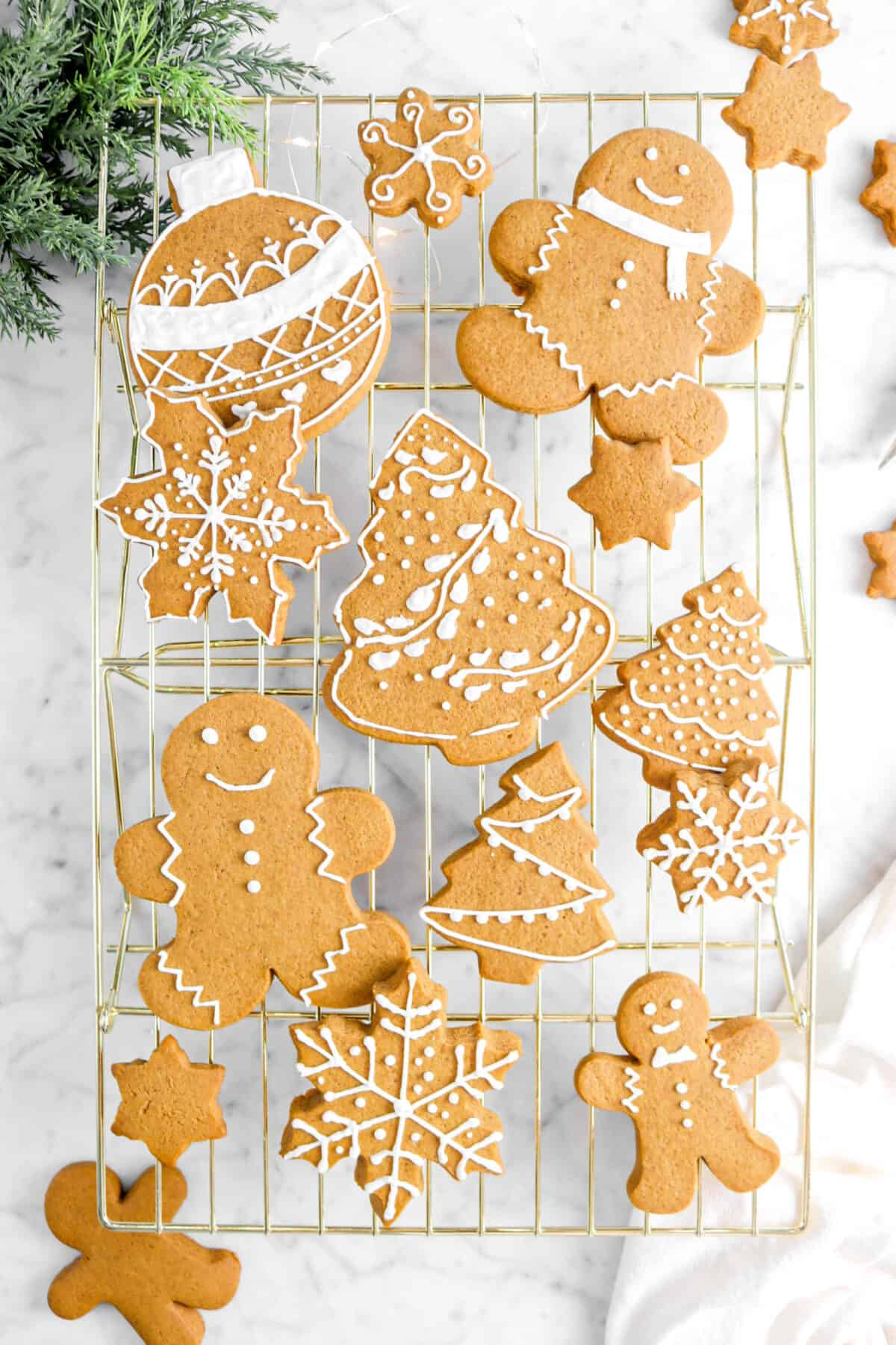 overhead shot of decorated gingerbread cookies on gold cooling rack