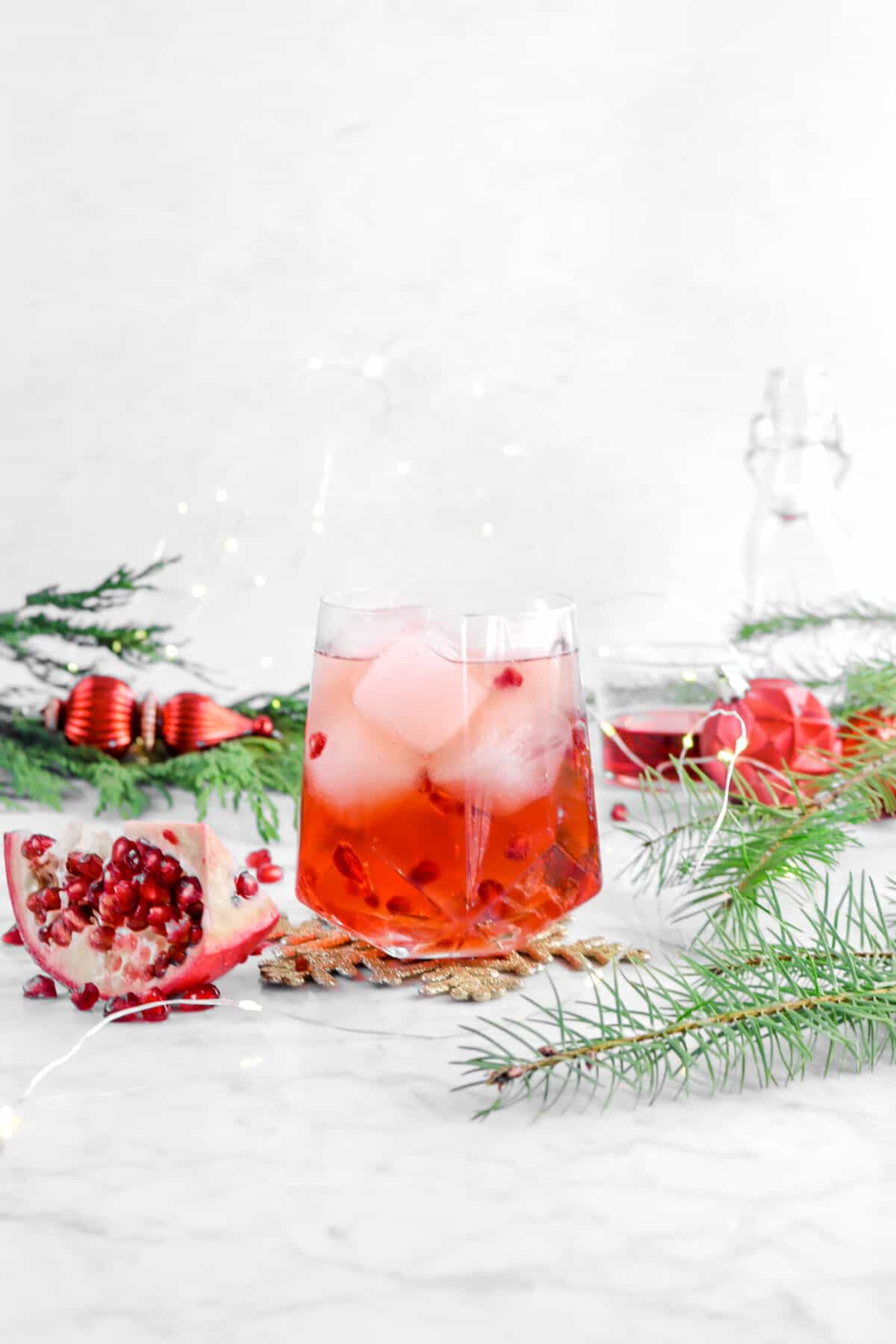 Pomegranate moscow mule with greenery, wedge of pomegranate, and fairy lights