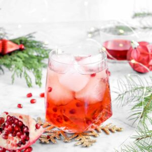 Pomegranate moscow mule with ornaments, greenery, fairy lights, and pomegranate wedge