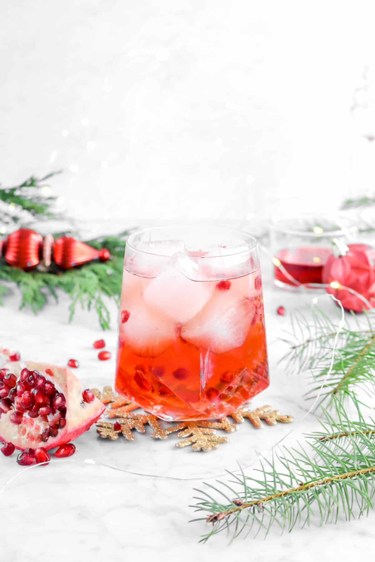 Pomegranate moscow mule on gold snowflake with red ornaments, greenery, and lights