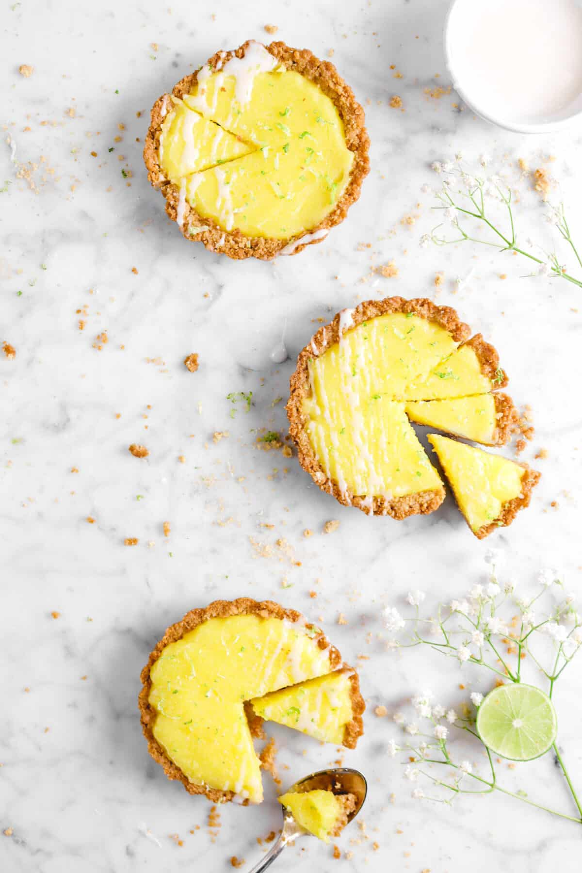 three slices key lime pies on marble with crumbs, flowers, and glzr