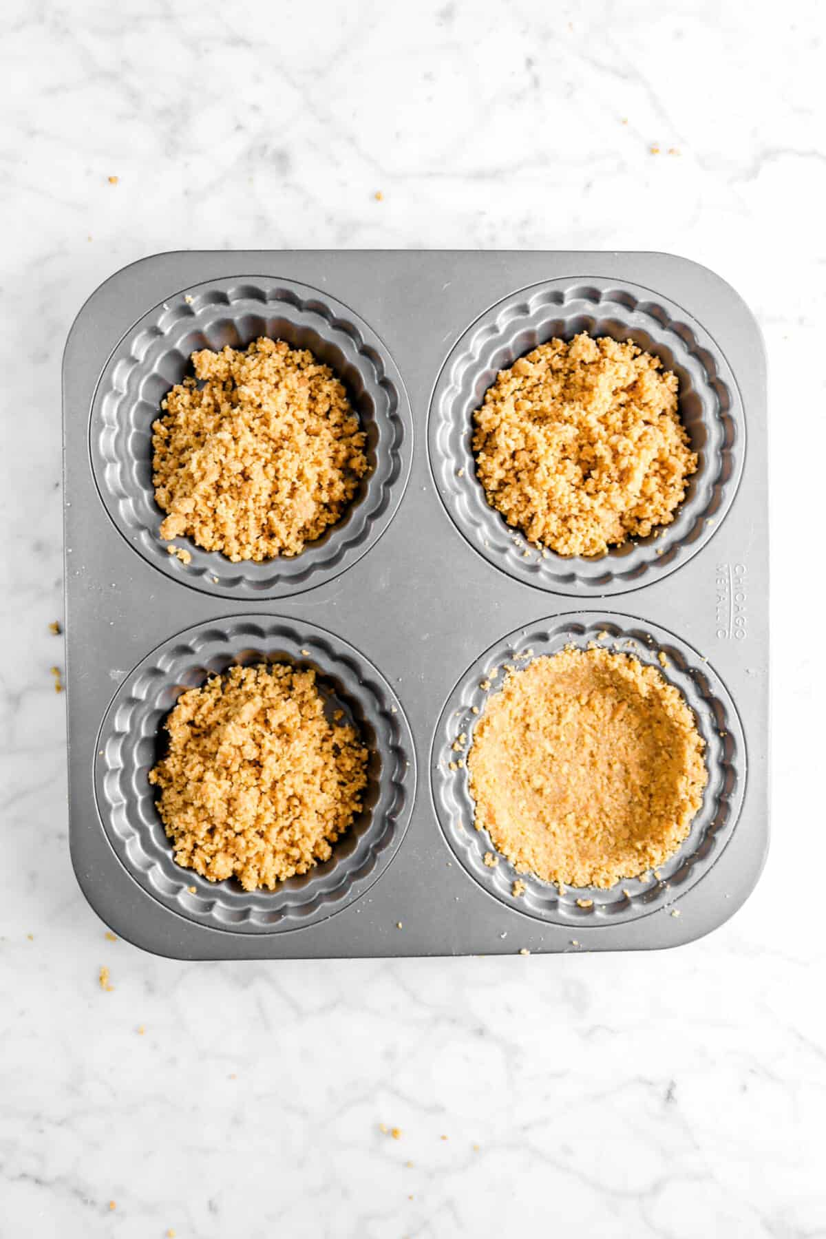 graham cracker crust in small tart pans with one pressed in