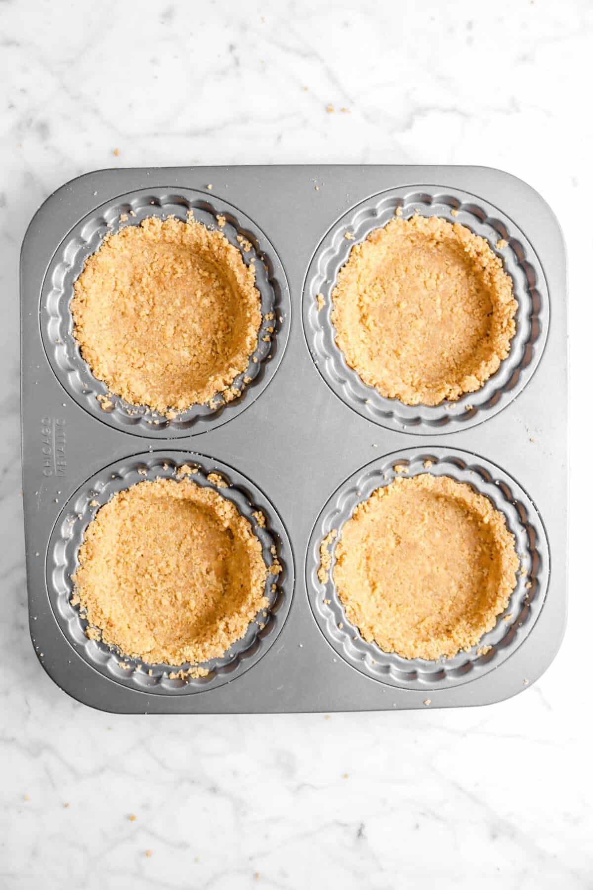 four graham cracker crusts in tart pans