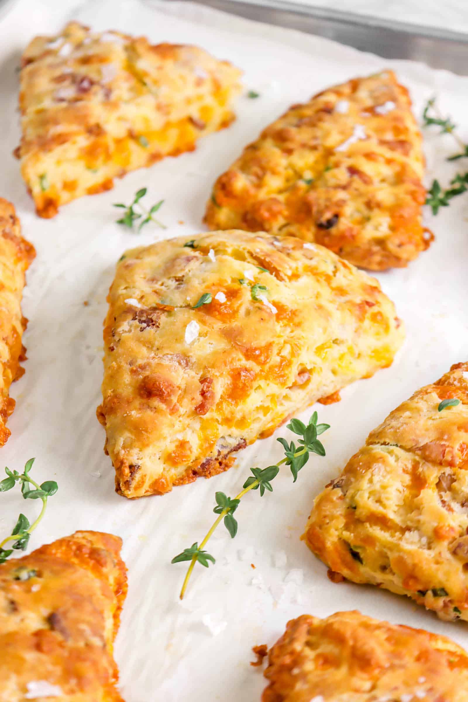 six scones on parchment paper with thyme sprigs and salt