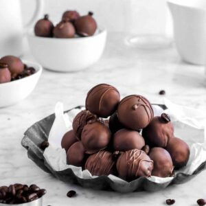 stacked coffee truffles on lined pan with coffee beans and more truffles behind