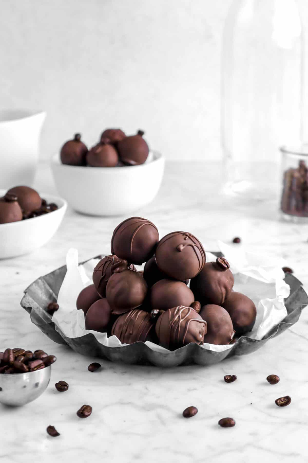 twelve coffee truffles on lined circle pie pan with coffee beans with more truffles and glass jar behind