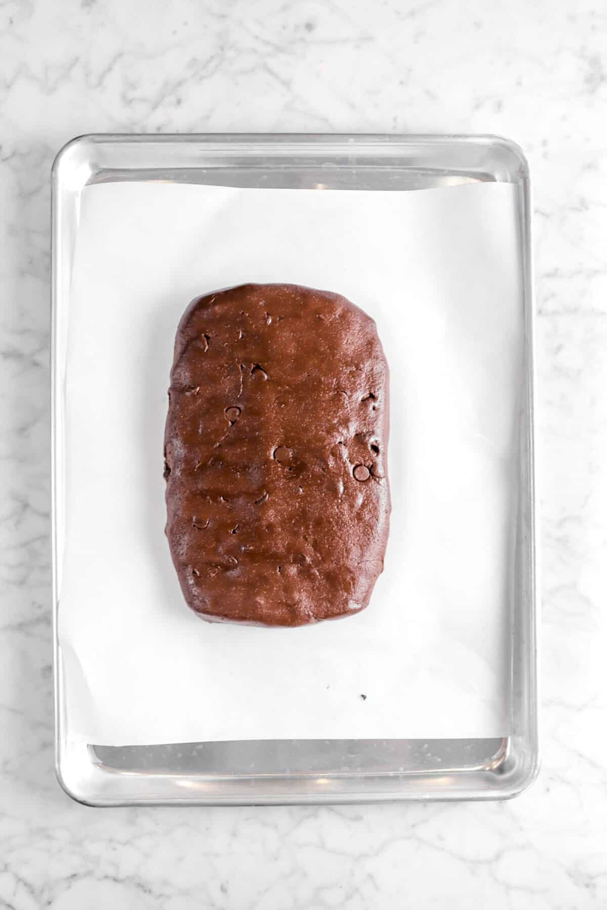 chocolate biscotti dough on lined baking sheet
