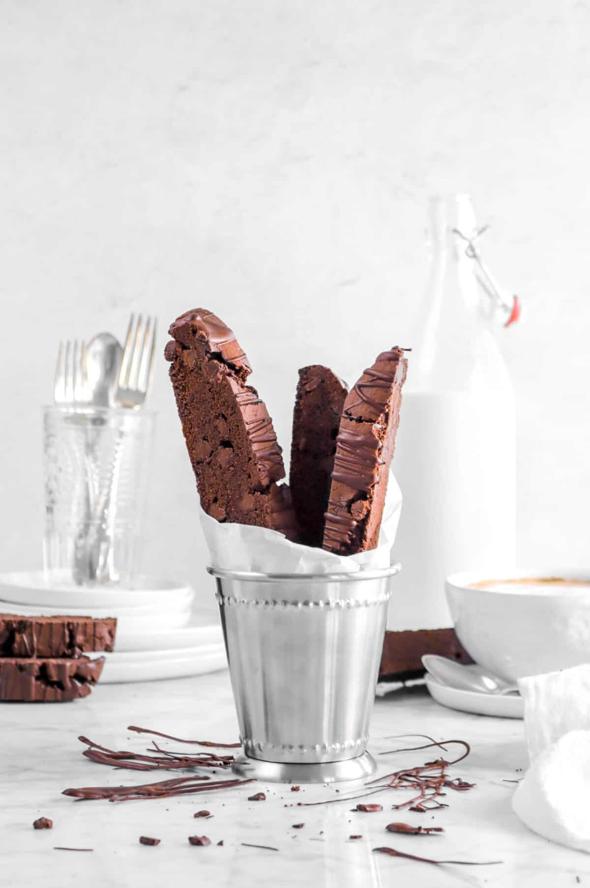 chocolate biscotti in metal cup with chocolate drizzle, a white napkin, mug of coffee, milk glass, and utensils behind