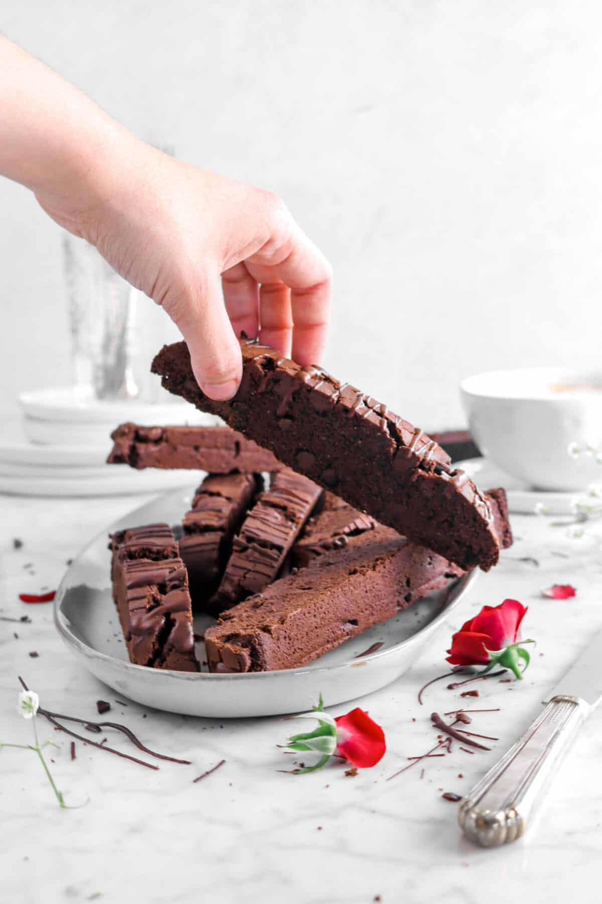 hand grabbing biscotti from serving plate with roses
