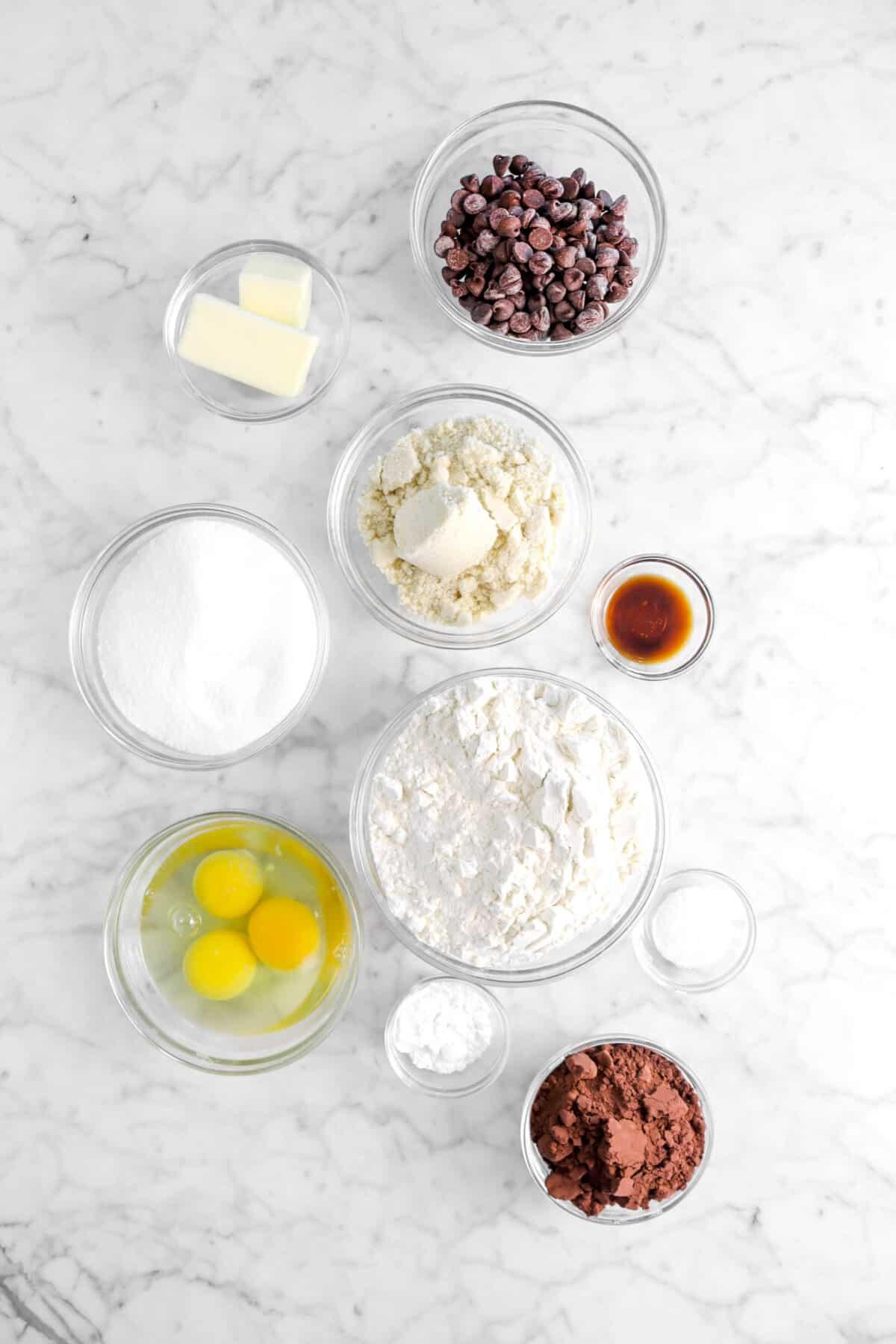 chocolate chips, butter, almond flour, vanilla, sugar, flour, eggs, salt, baking powder, and cocoa powder in glass bowls