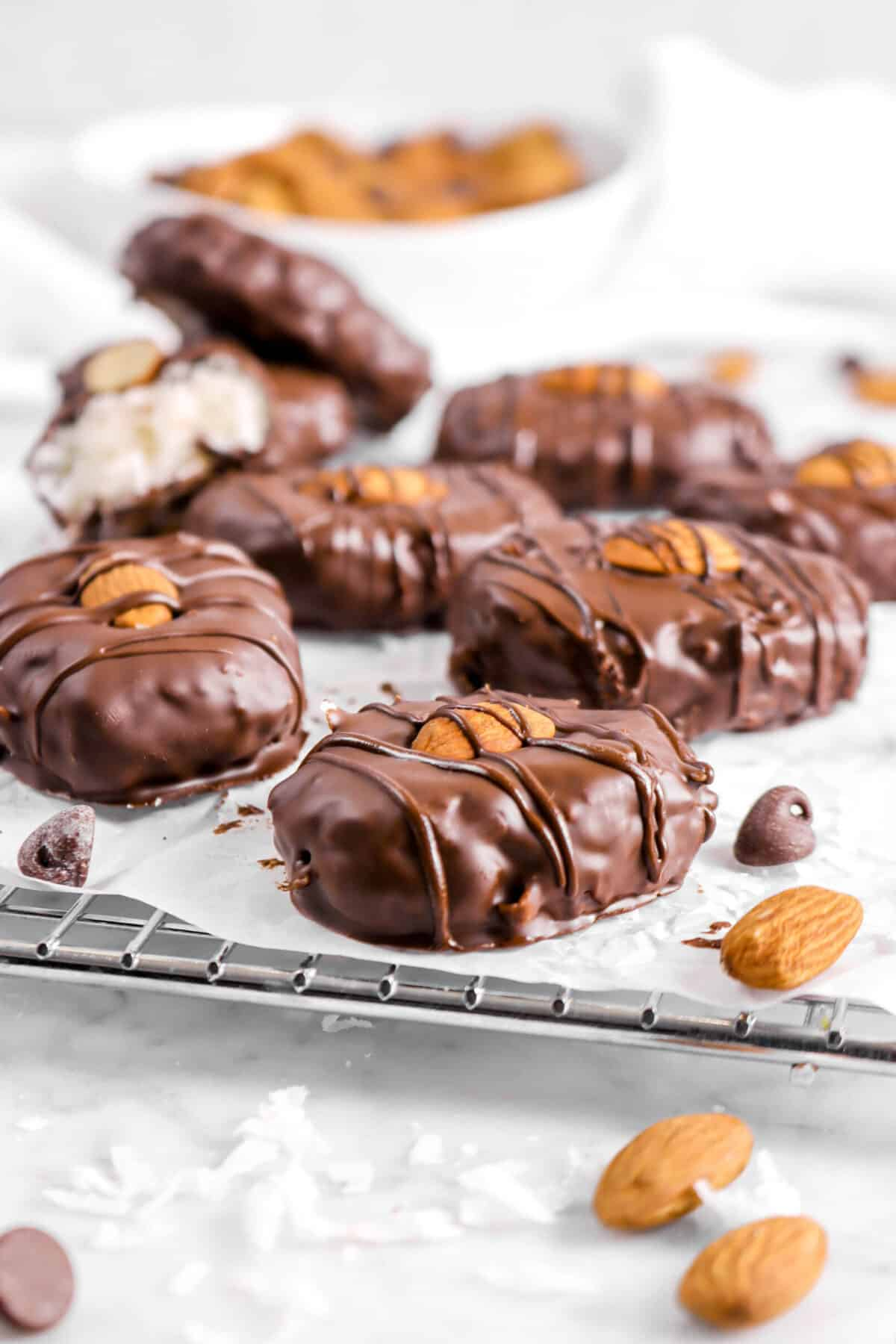 eight almond joys on a cooling rack with almonds and chocolate chips