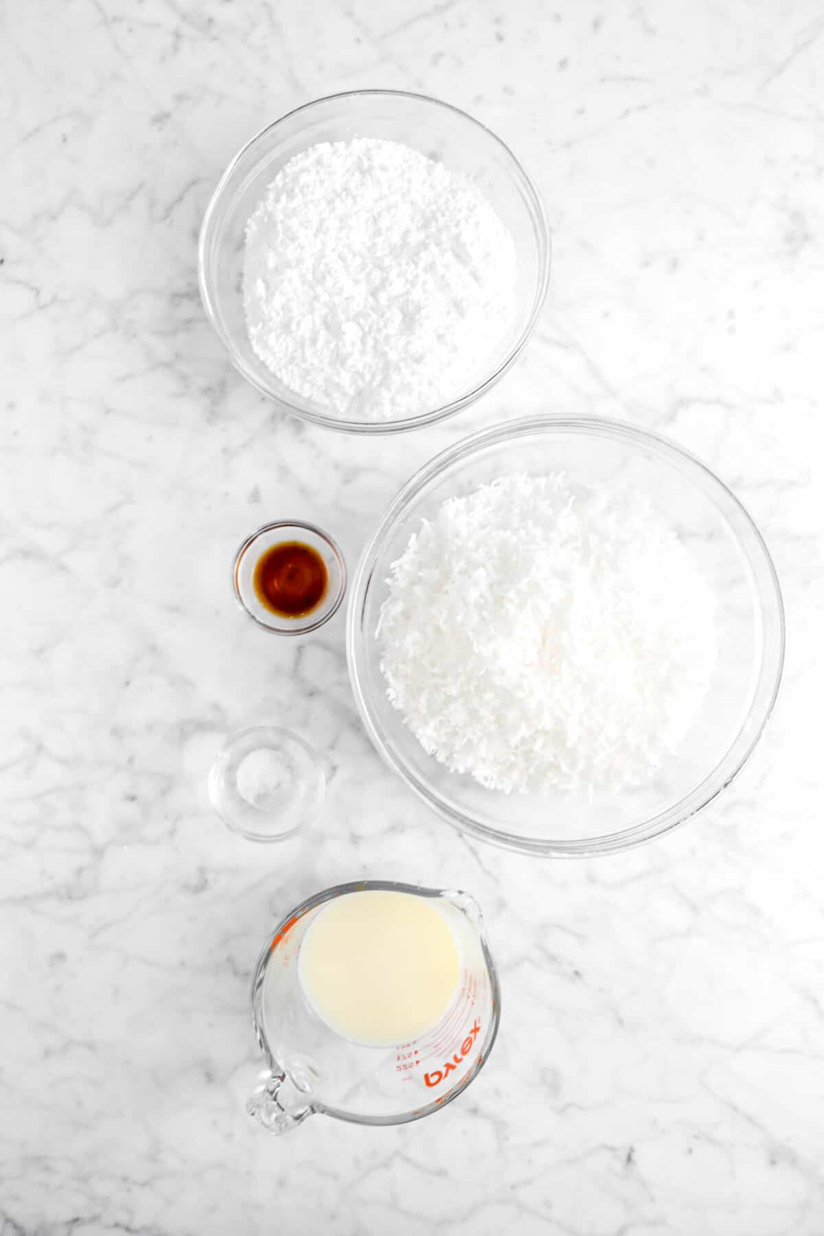 powdered sugar, coconut flakes, vanilla, salt, and condensed milk on marble counter