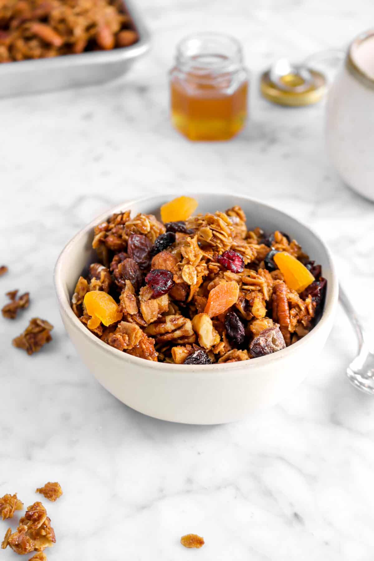 small bowl of granola with dried fruit on with small pot of honey behind