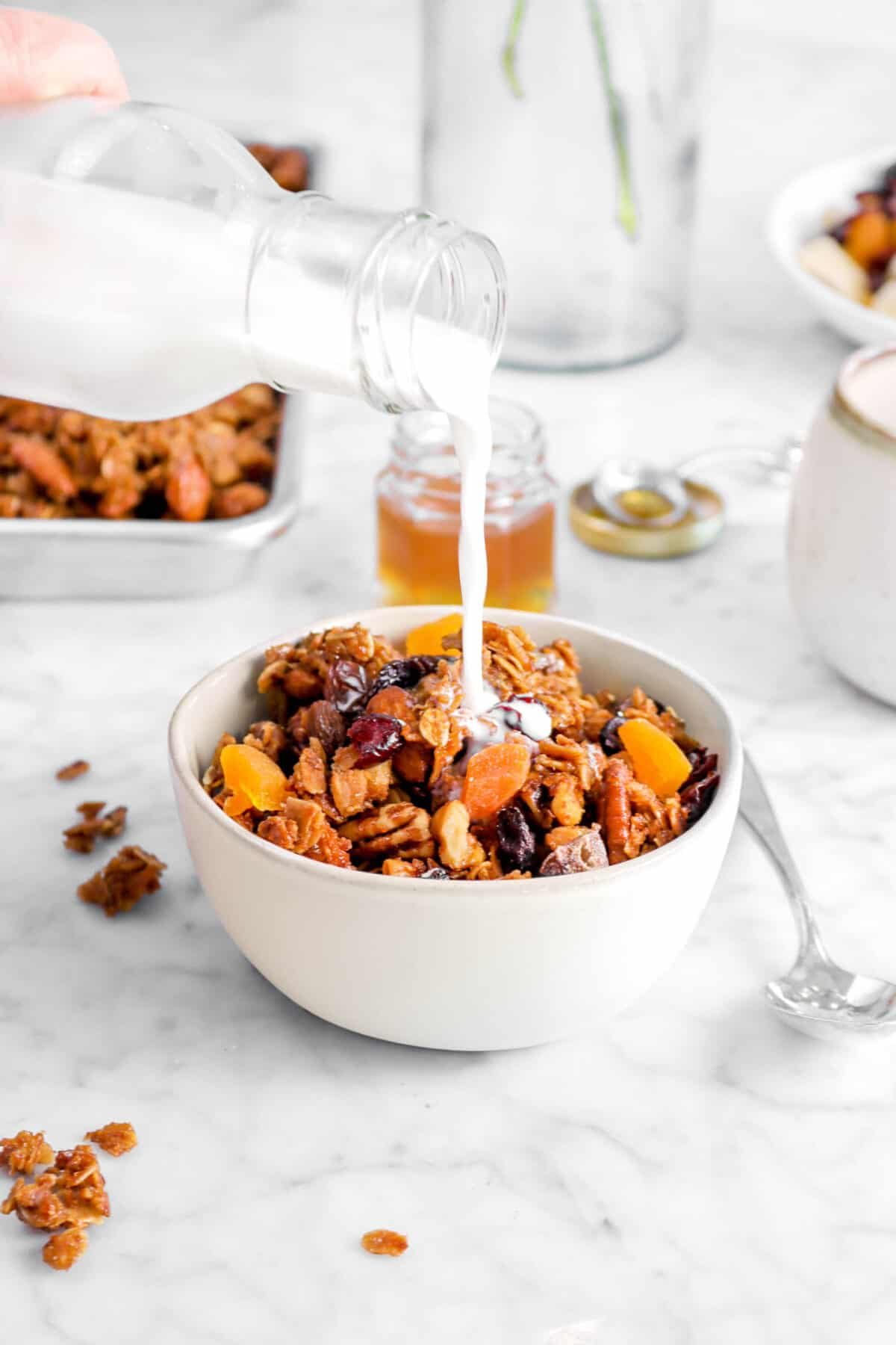 milk being poured into bowl of granola with small jar of honey behind