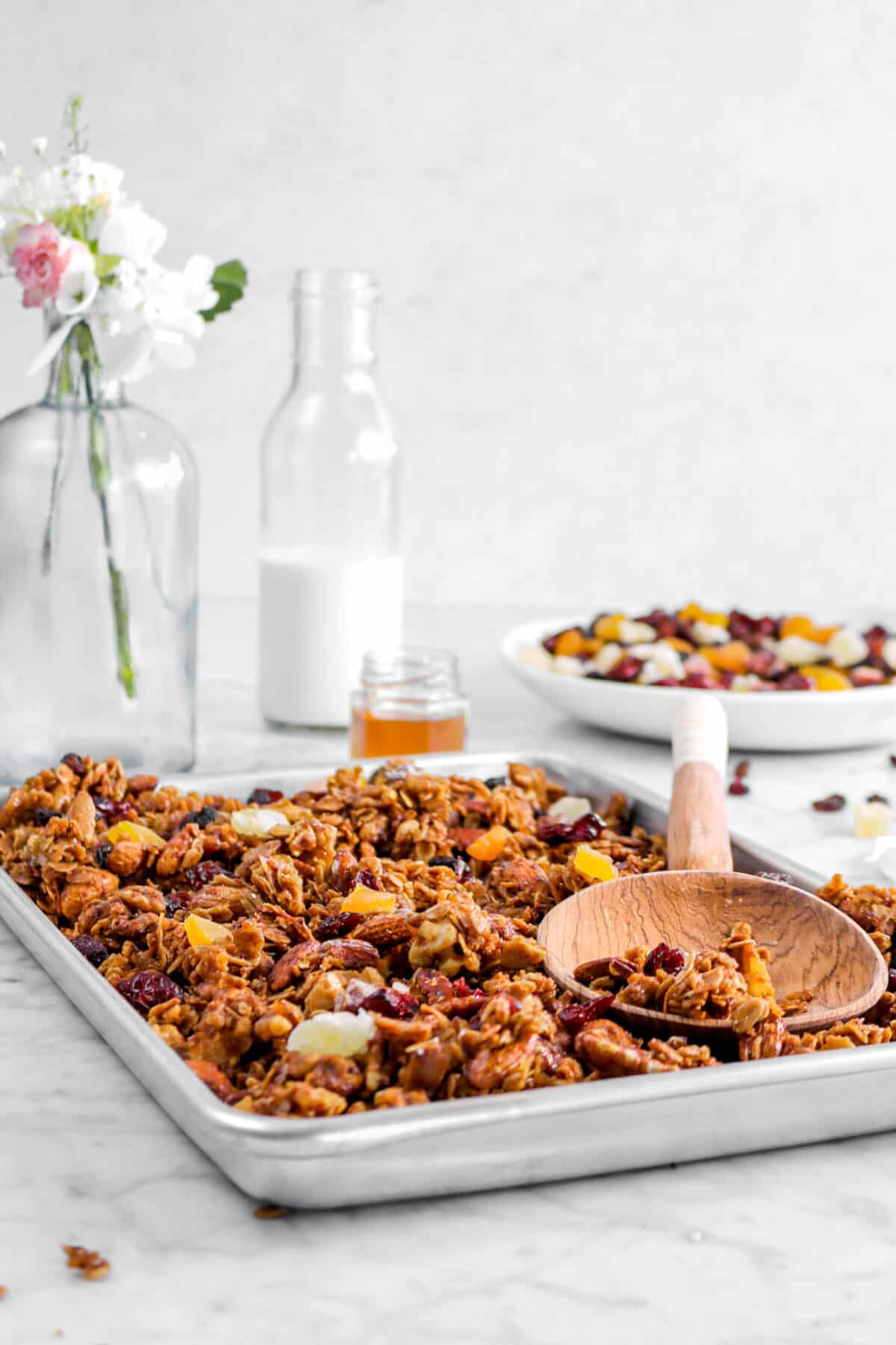 sheet pan full of granola with wooden spoon, flowers, honey jar, glass of milk, and dried fruit bowl