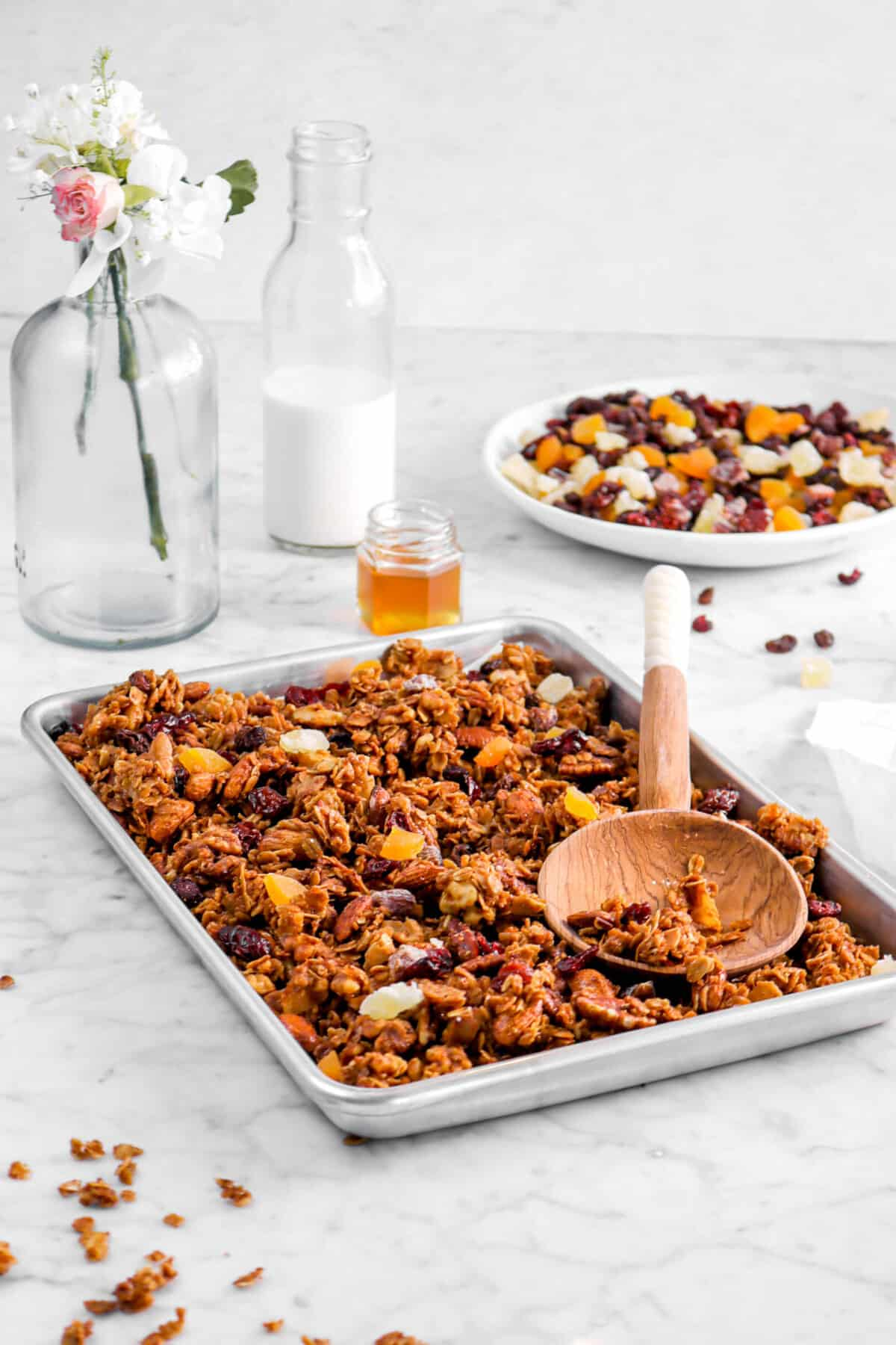 granola in sheet pan with wooden spoon, bowl of dried fruit, milk glass, honey pot, and flowers